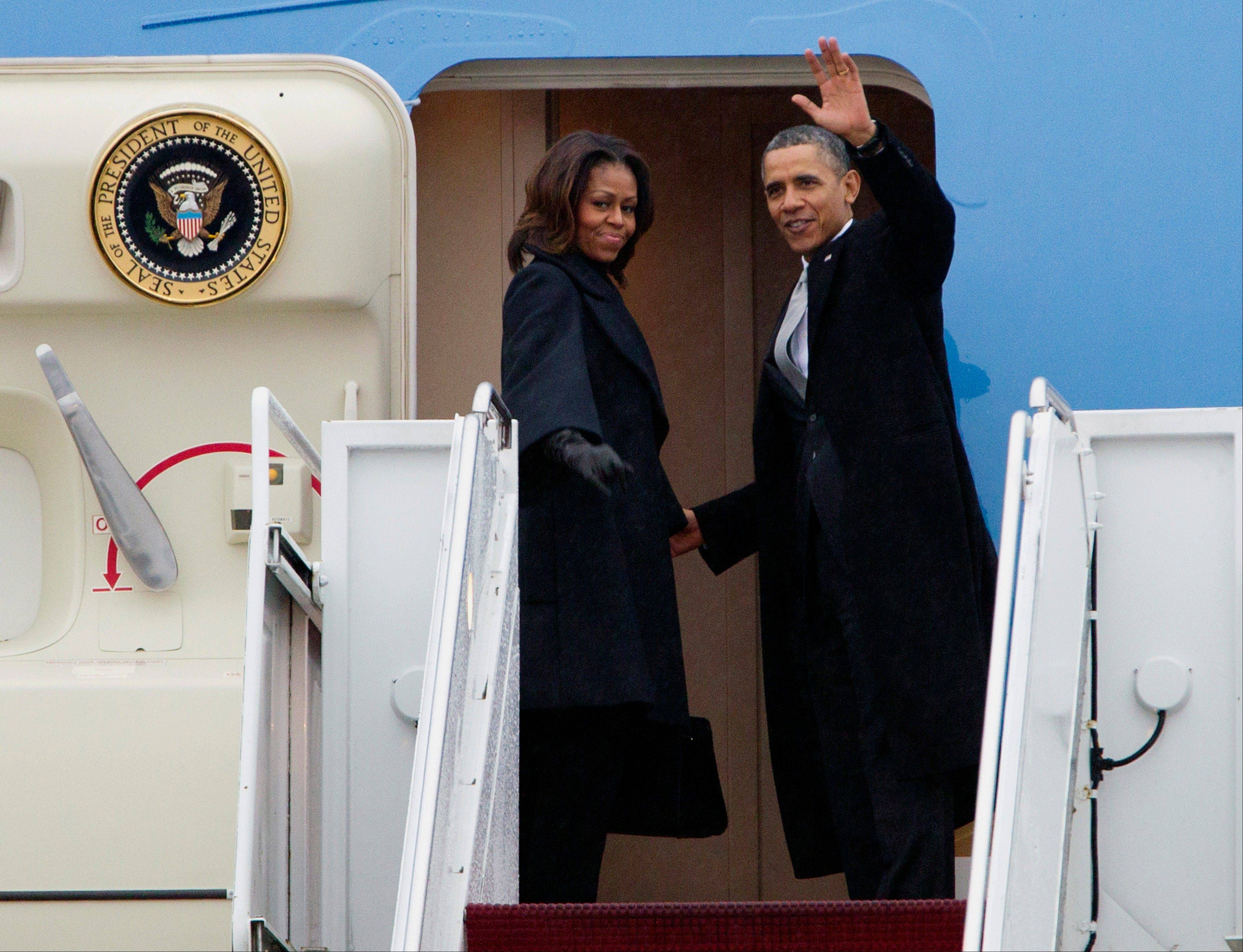 President Barack Obama, accompanied by first lady Michelle Obama, waves prior to boarding Air Force One at Andrews Air Force Base, Md., Monday before traveling to South Africa for a memorial service in honor of Nelson Mandela.