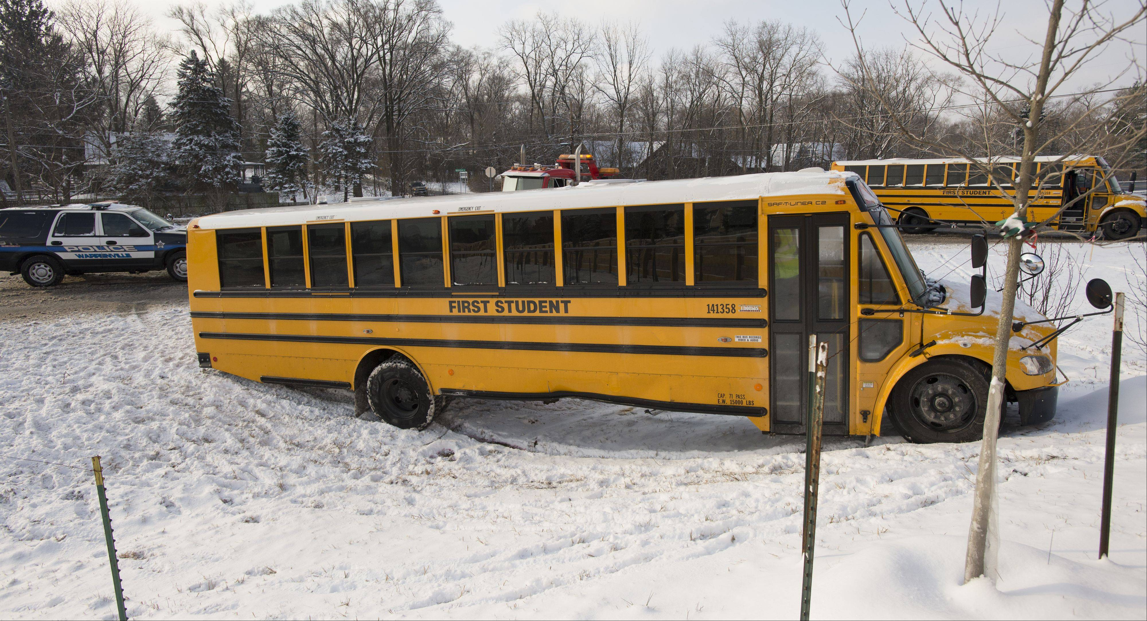 Students board a second school bus Monday morning after the bus in which they were riding wound up in a ditch along Butterfield Road in Warrenville.