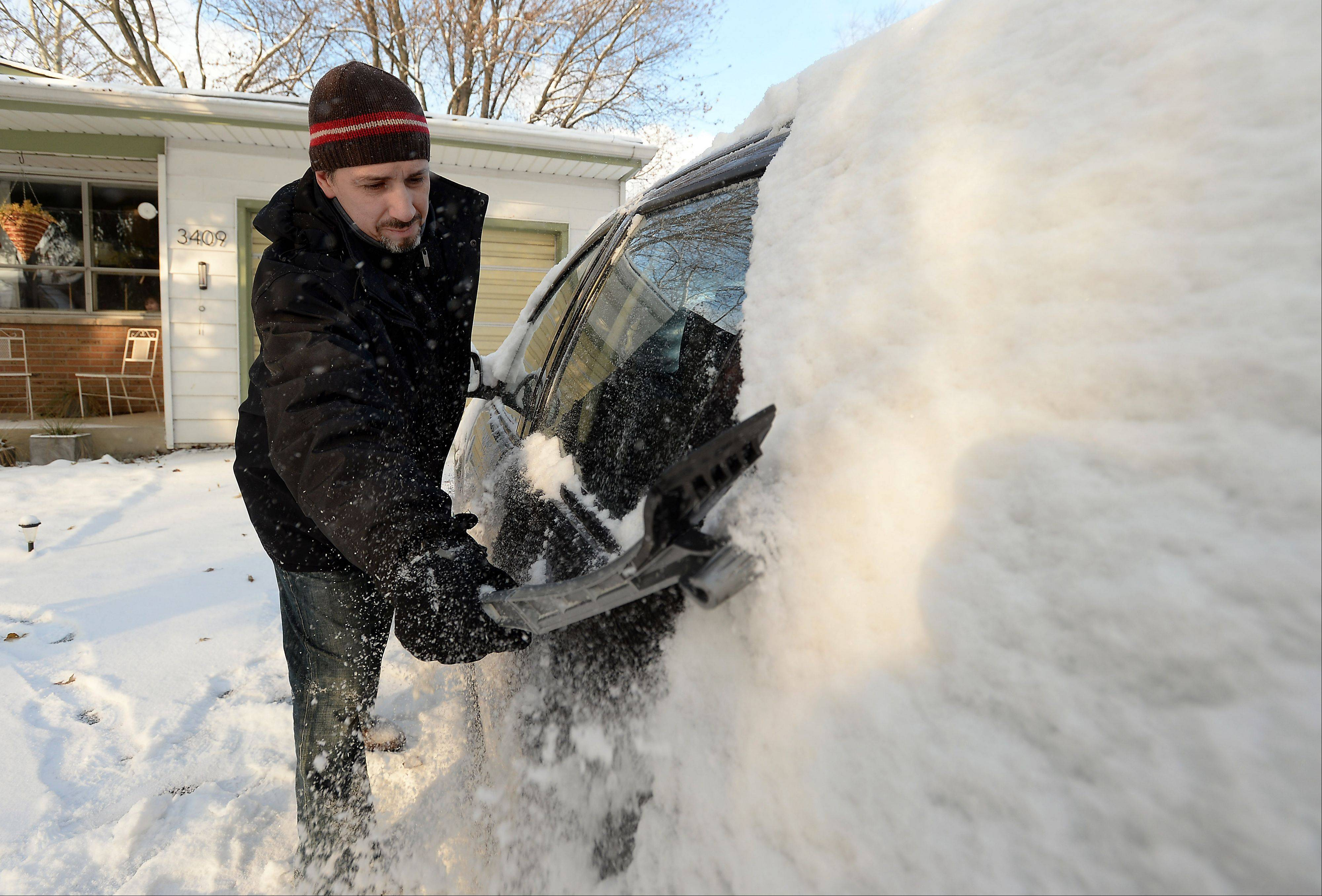 "Allen Garcia of Rolling Meadows says he ""loves the snow"" as he cleans off his cars Monday, a day after the Northwest suburbs saw about three inches fall on the region."