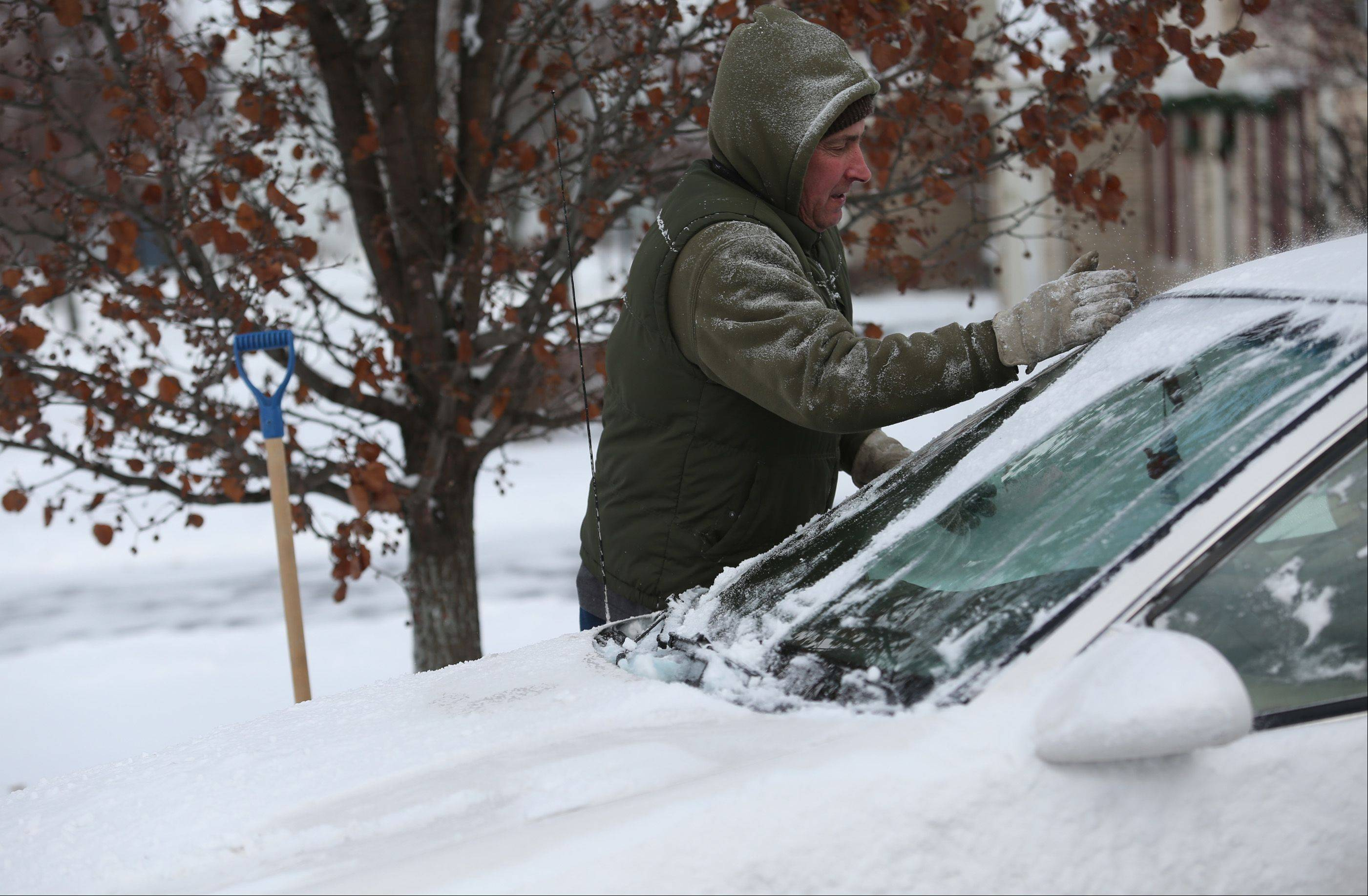 "Algonquin resident Rick Klewin clears the windshield of his car Monday morning. Klewin said he was disappointed there wasn't more than just a few inches of snow. ""I love snow,"" Klewin said, ""This is nothing."" He added that he was jealous that areas to the north received more snow, particularly in Wisconsin."