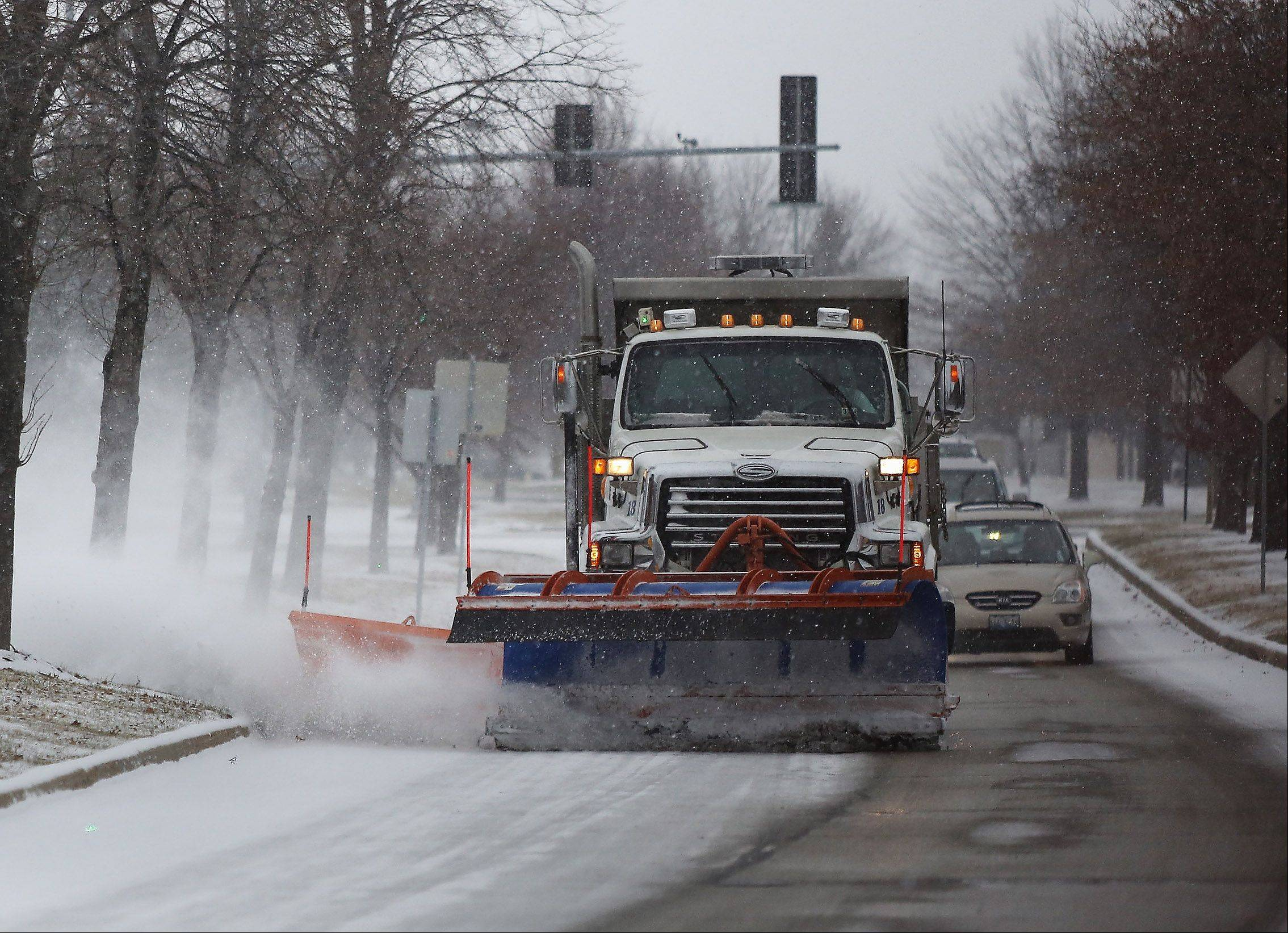A Vernon Hills Public Works snowplow clears the Fairway Drive as snow blanketed the suburbs on Sunday.