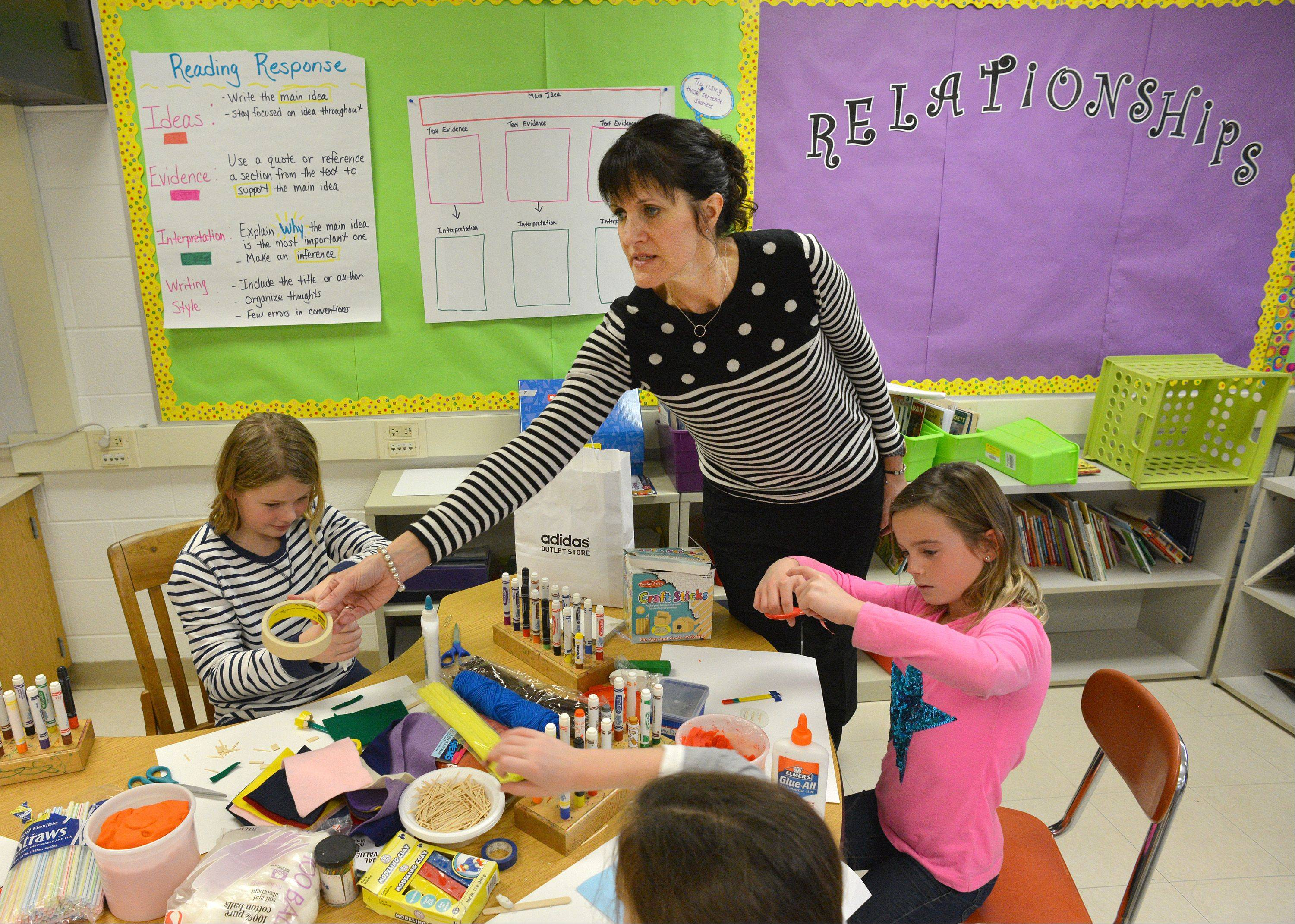 Third-grade literacy teacher Michelle Spratt helps students Kennedey Brandt, left, and Sophia Brown learn about relationships at Benjamin Franklin Elementary School in Glen Ellyn. The school recently was honored for its innovative approaches to learning.