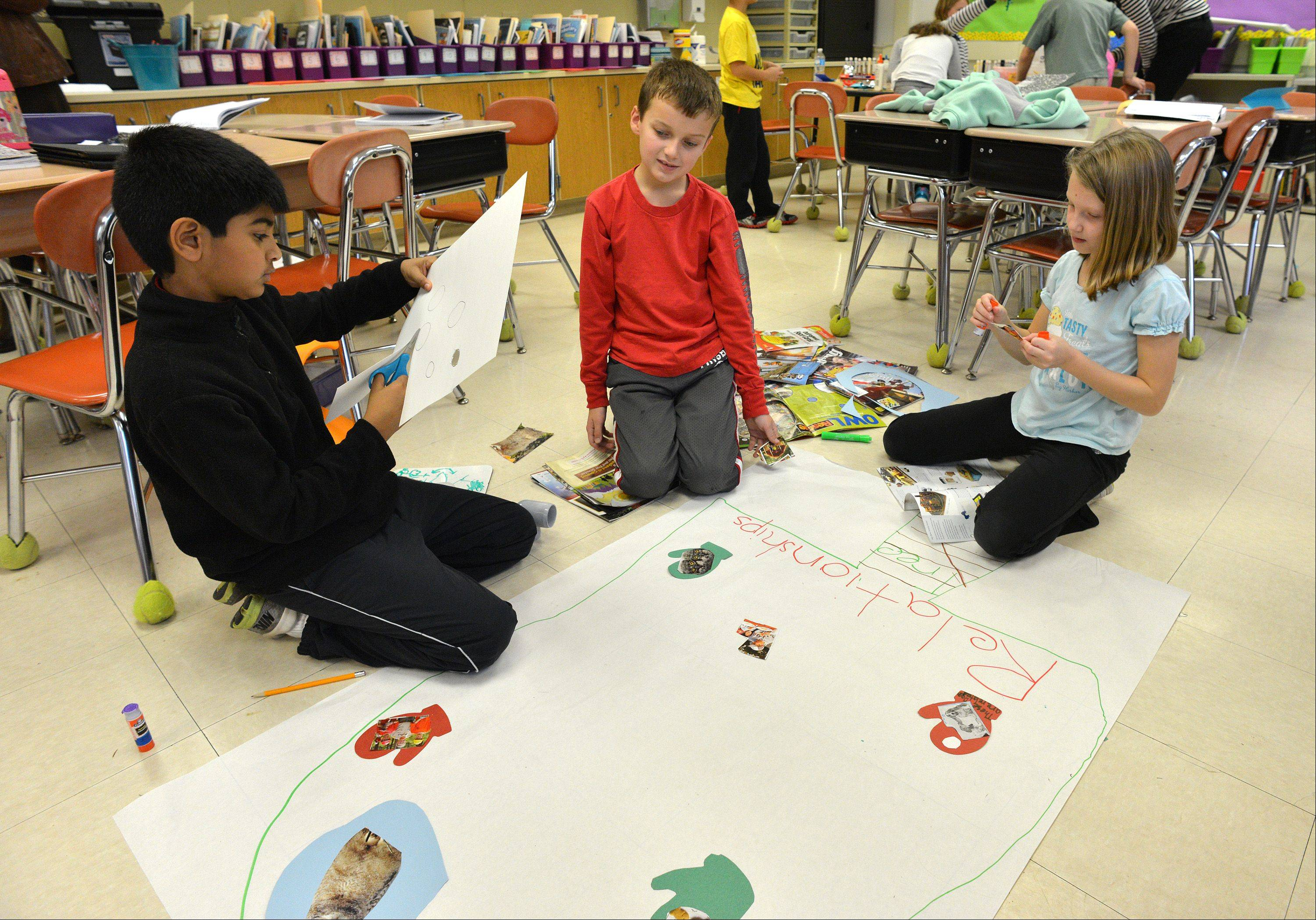 "Aarav Pathak, left, Charlie VanEk and Paige Legel, students at Benjamin Frankling Elementary School in Glen Ellyn, make a ""Relationship Tree"" with cutouts of objects that relate to each other. The school recently was honored for its innovative approaches to learning."