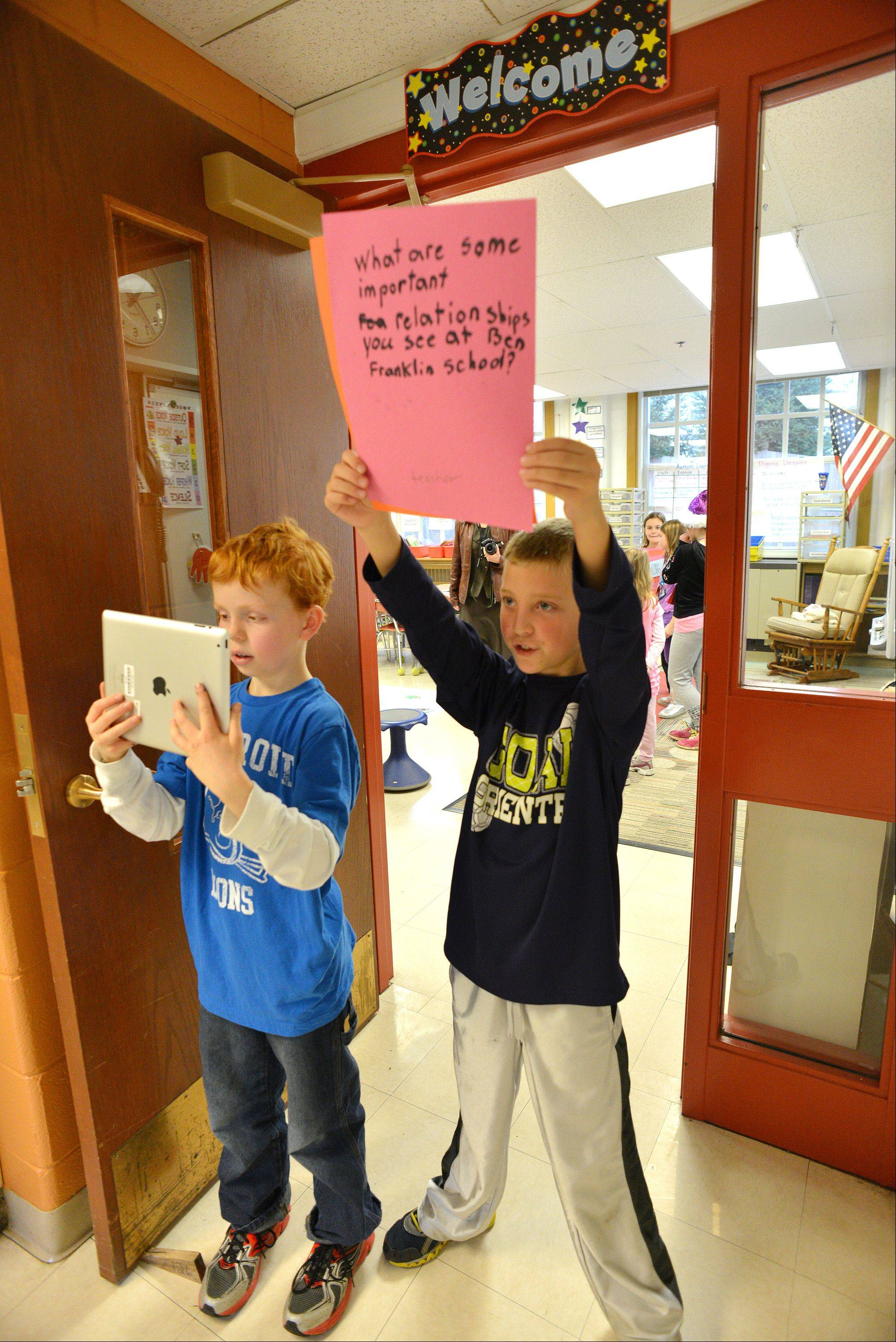 Some students at Benjamin Frankling Elementary School in Glen Ellyn are making videos asking people about their relationships. Nathan Hibbard, left, records a video on an iPad, while Andrew Novak holds cue cards for the actors. The school recently was honored for its innovative approaches to learning.