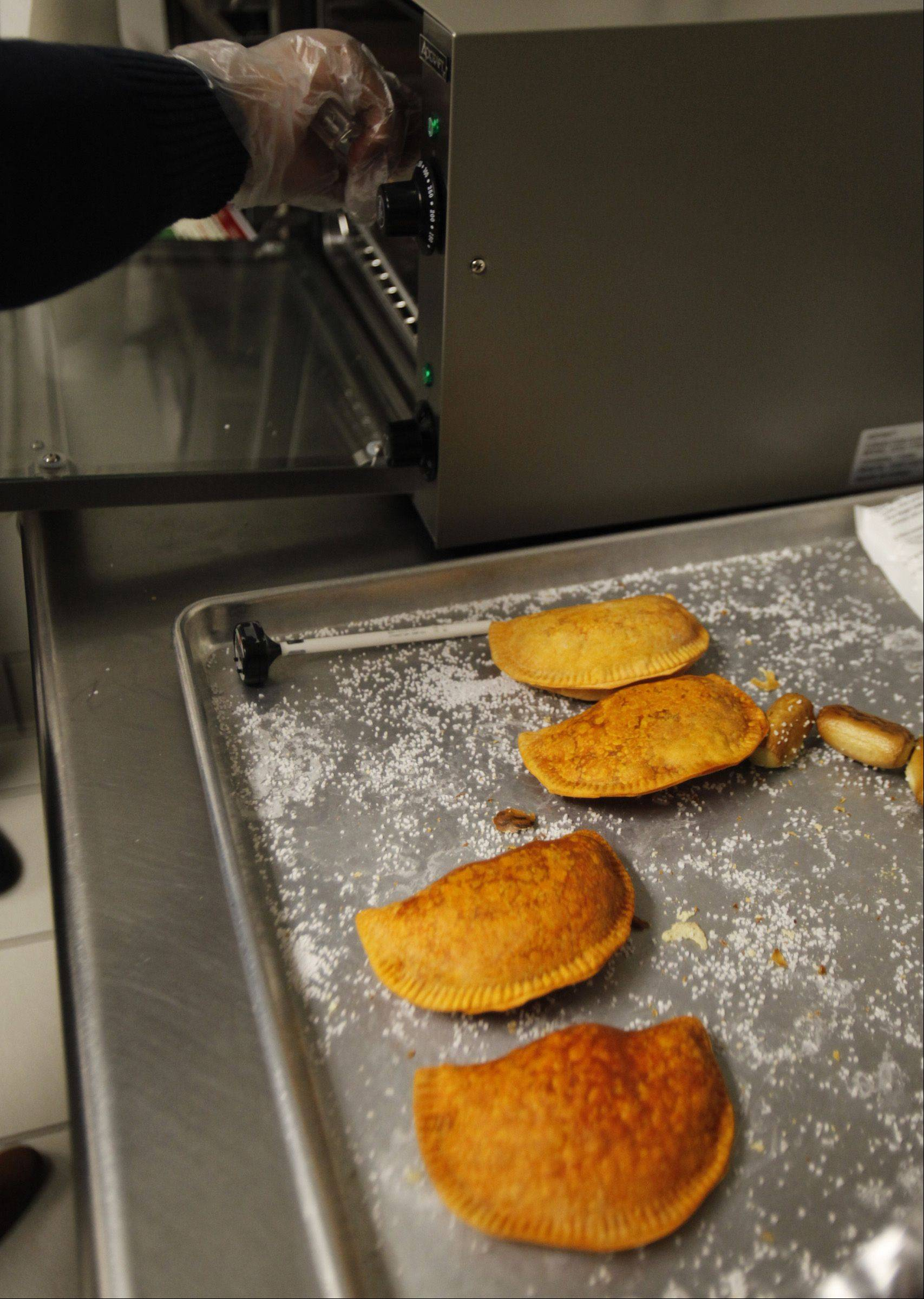 Kevin Echevarria removes some empanadas from an oven last Friday morning at Classic Cinemas' Charlestowne 18 in St. Charles. The movie theater began selling Rria Foods' empanadas that day on a trial basis. The company will follow suit at more locations if sales go well, the theater's general manager said.