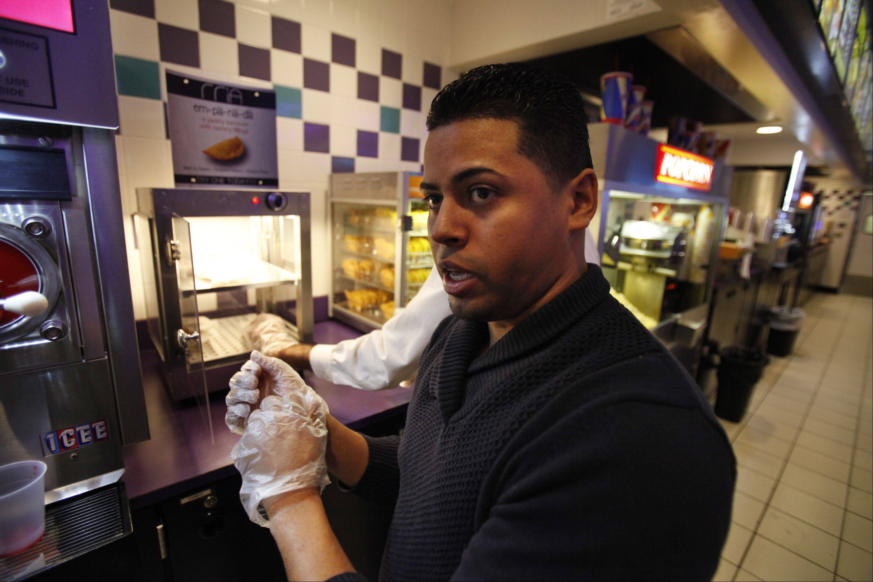 Kevin Echevarria, co-owner of Rria Foods in Elgin, talks with Randy Pollock, the general manager at Classic Cinemas' Charlestowne 18 in St. Charles, which began selling Rria Foods' empanadas last week. Echevarria believes empanadas will become mainstream like burritos.
