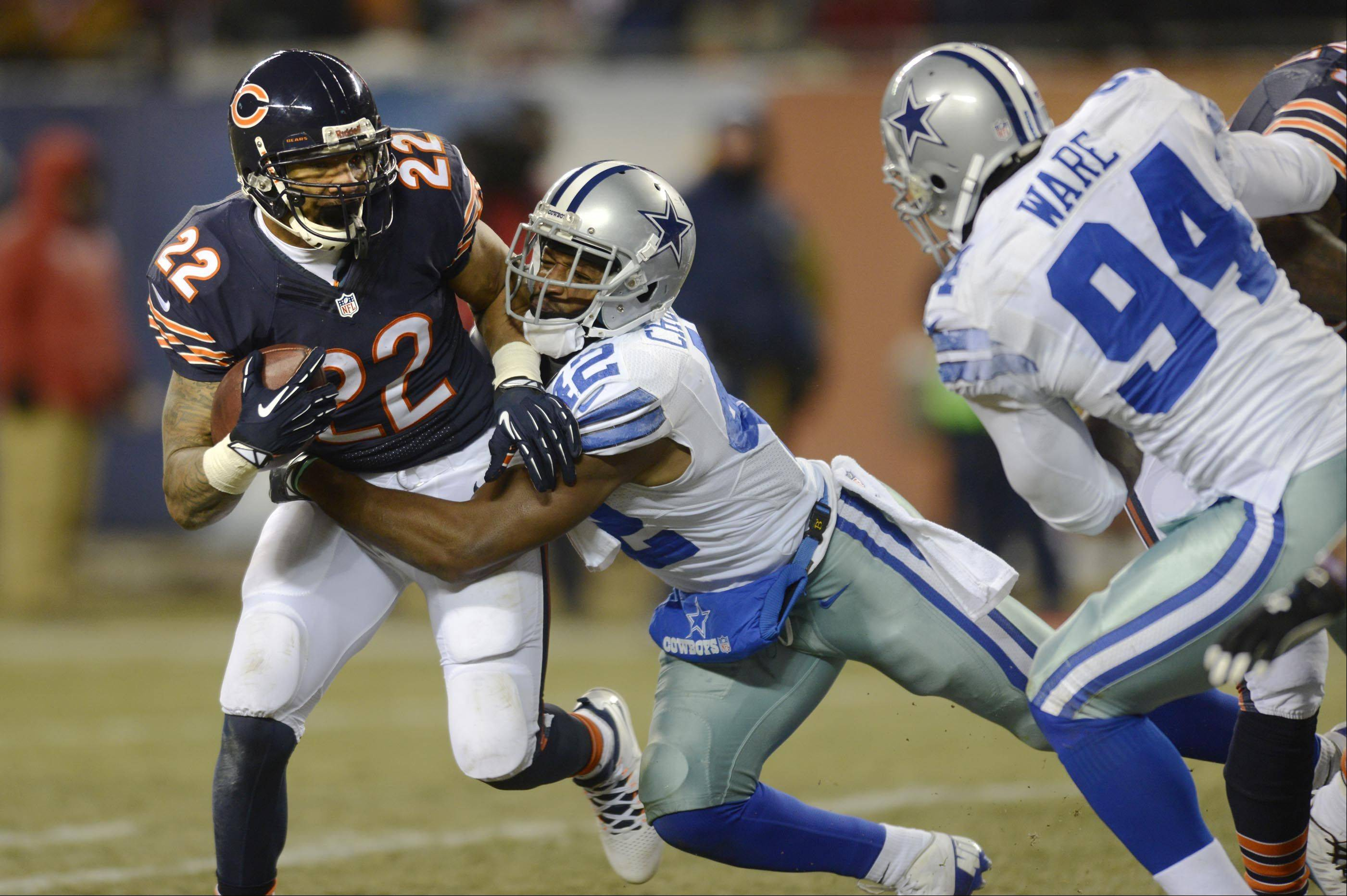 Chicago Bears running back Matt Forte tries to break away from Dallas Cowboys free safety Barry Church as Cowboys defensive end DeMarcus Ware fights a block.