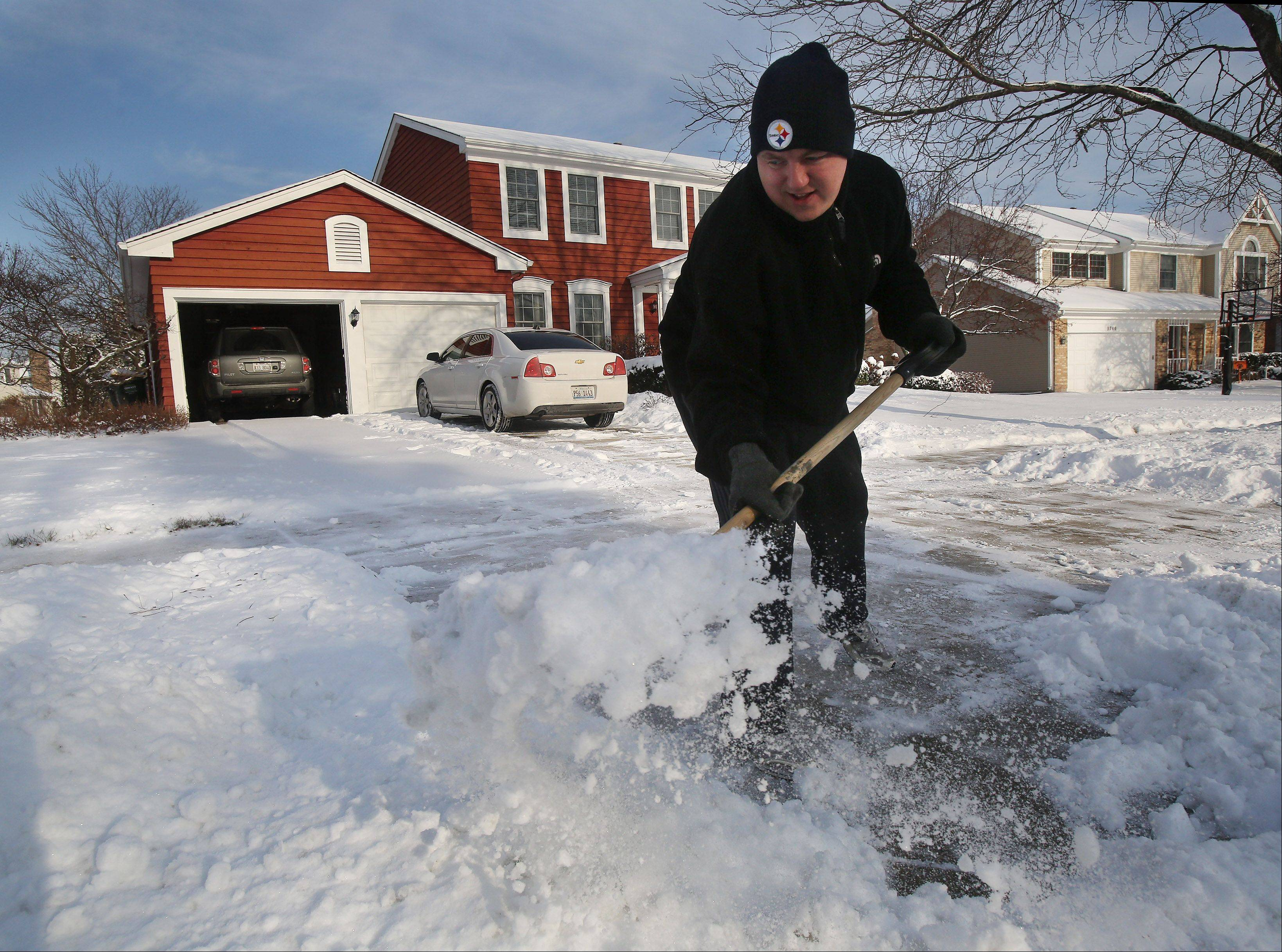 Libertyville resident Rocky Hakanen shovels snow off his driveway Monday morning after the first significant snowfall of the year in Lake County.