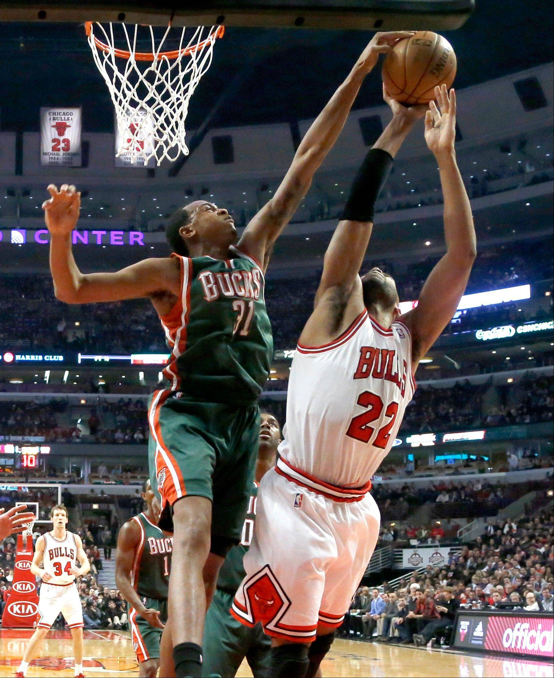 Milwaukee Bucks forward John Henson (31) blocks the shot of Chicago Bulls forward Taj Gibson (22) during the first half of an NBA basketball game Tuesday, Dec. 10, 2013, in Chicago.