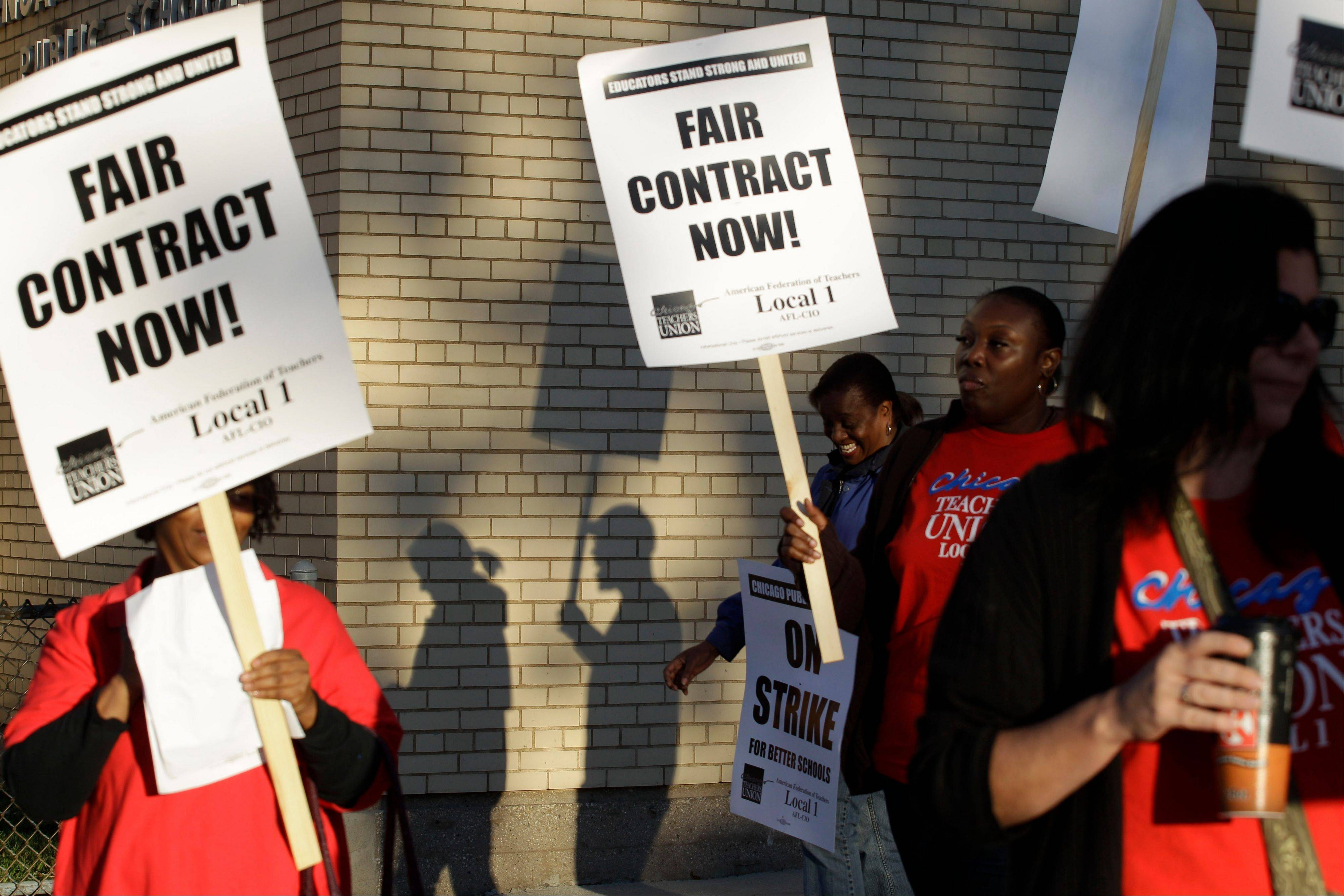 This Sept. 10, 2012 photo shows Chicago teachers walk walking a picket line outside a school in Chicago, after they went on strike for the first time in 25 years.