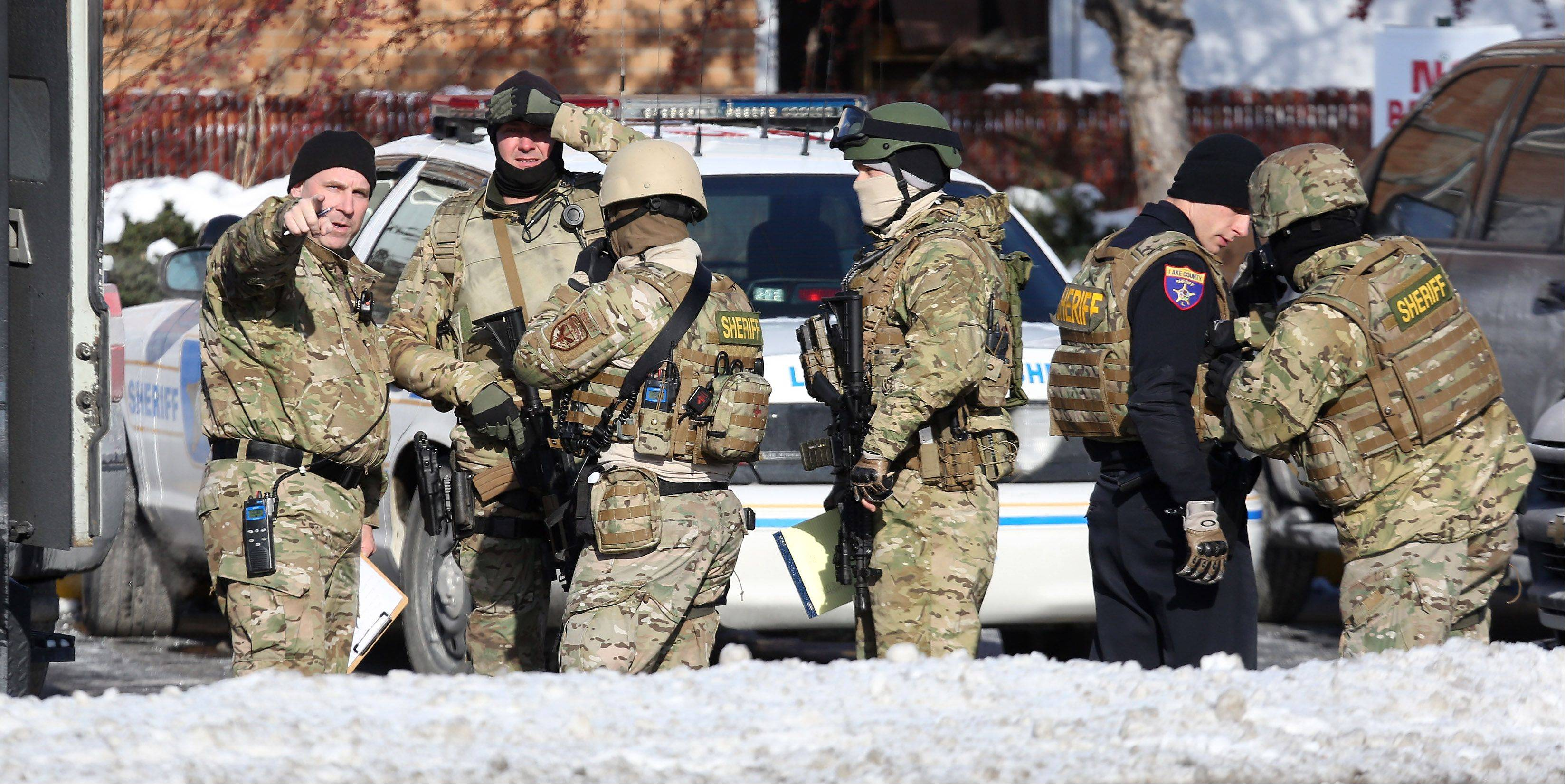 The Lake County incident response team members gear up Tuesday as they responded to a report of a man with a rifle barricaded in a house in Lake Villa. Local schools were in lockdown in response to the situation.