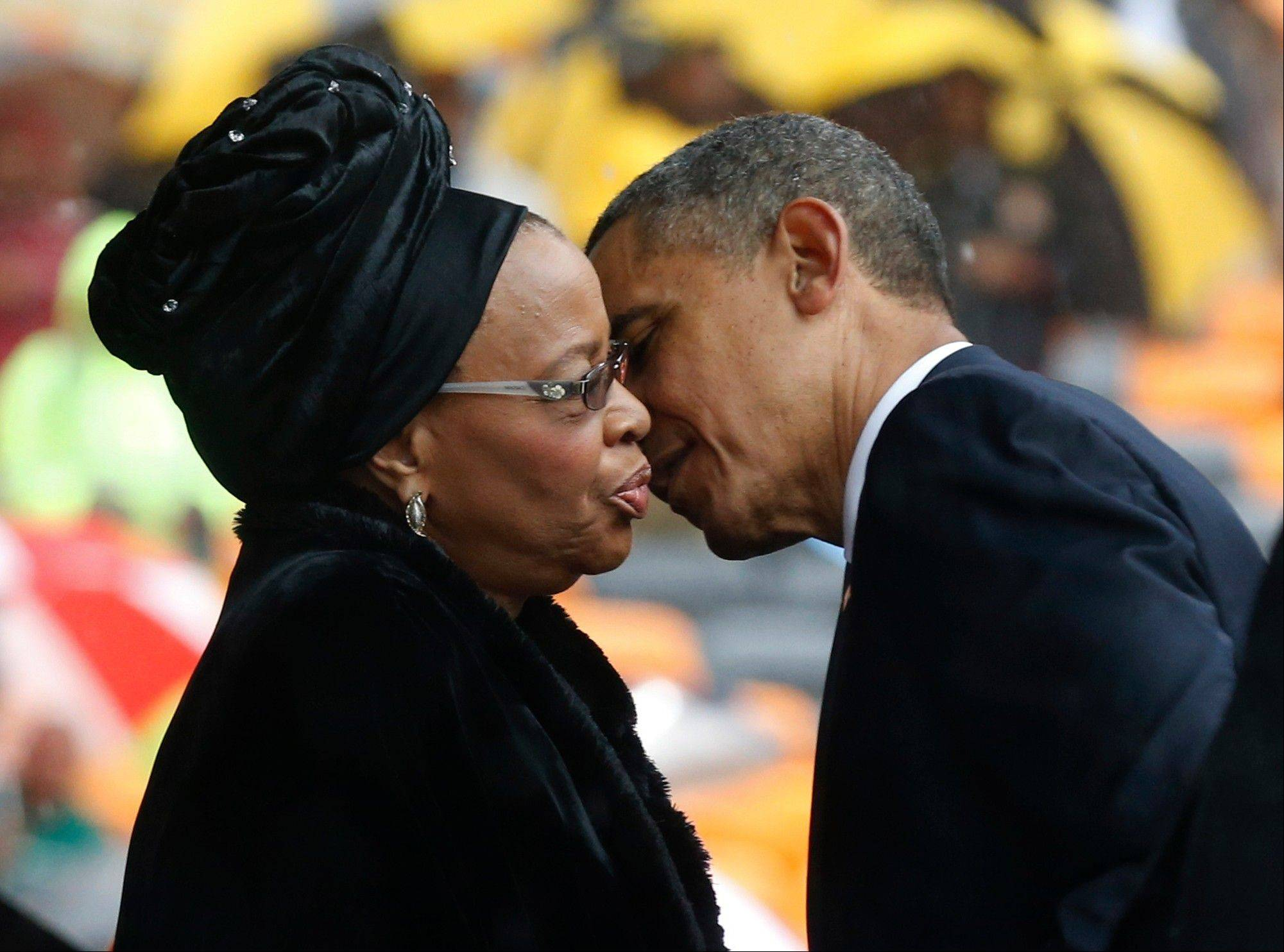 President Barack Obama kisses Nelson Mandela's widow Graca Machel during the memorial service for former South African President Nelson Mandela at the FNB Stadium in Soweto near Johannesburg, Tuesday, Dec. 10, 2013.