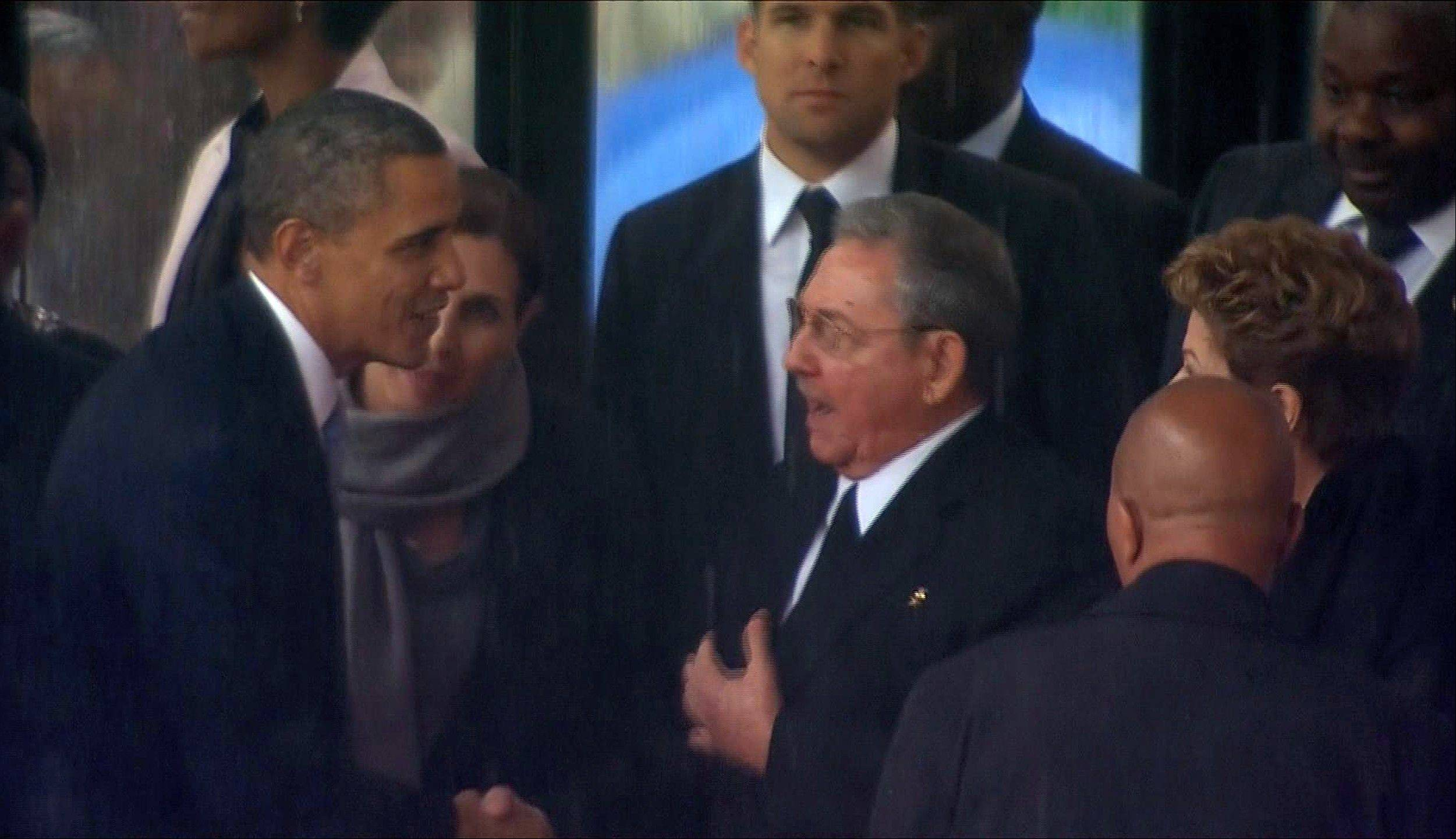 In this image from TV, U.S. President Barack Obama shakes hands with Cuban President Raul Castro at the FNB Stadium in Soweto, South Africa, in the rain for a memorial service for former South African President Nelson Mandela, Tuesday Dec. 10, 2013. The handshake between the leaders of the two Cold War enemies came during a ceremony that's focused on Mandela's legacy of reconciliation.