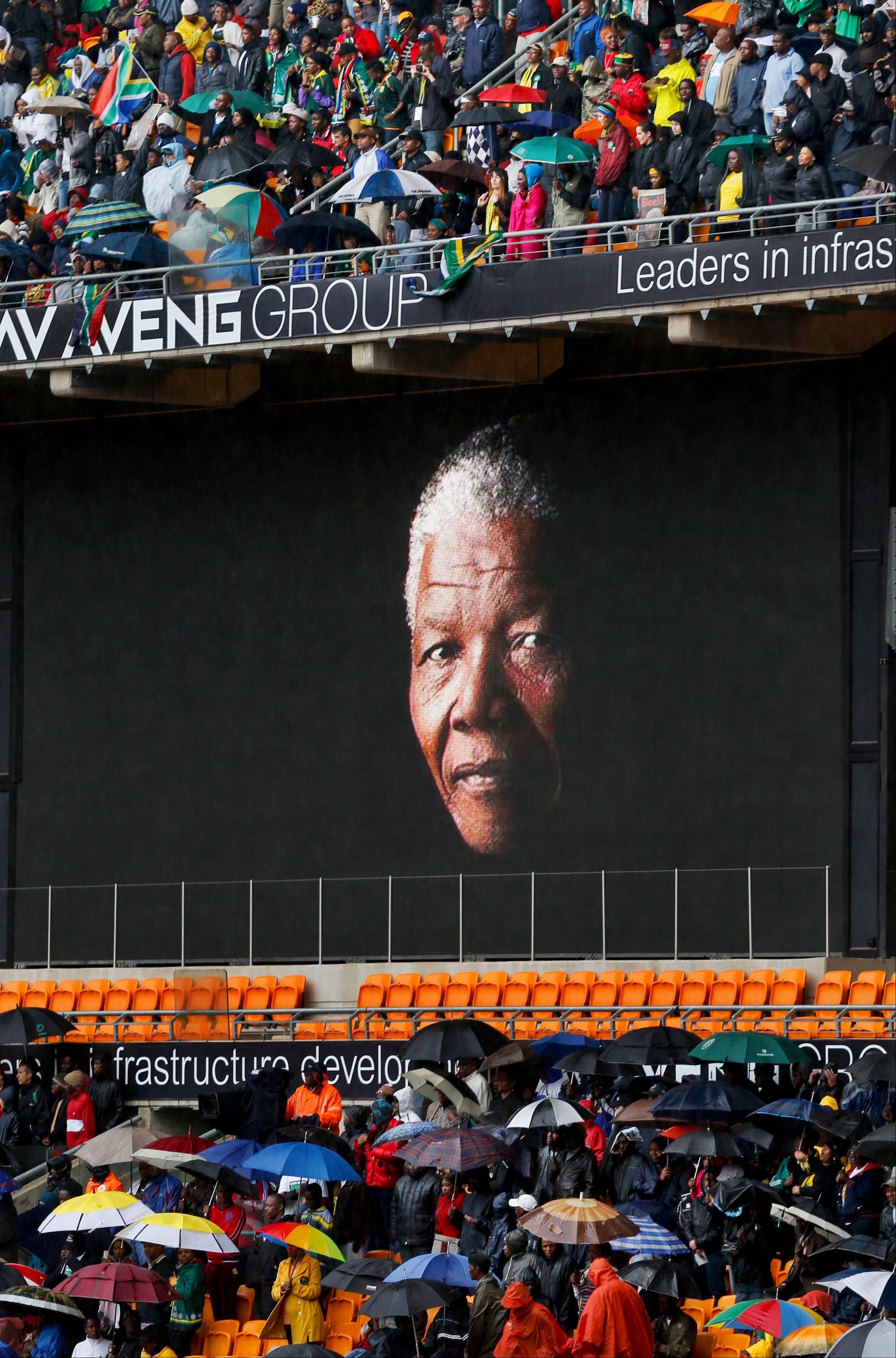 The face of Nelson Mandela is shown on a large billboard in the stands at the memorial service for former South African President Nelson Mandela at the FNB stadium in Johannesburg, South Africa Tuesday, Dec. 10, 2013.