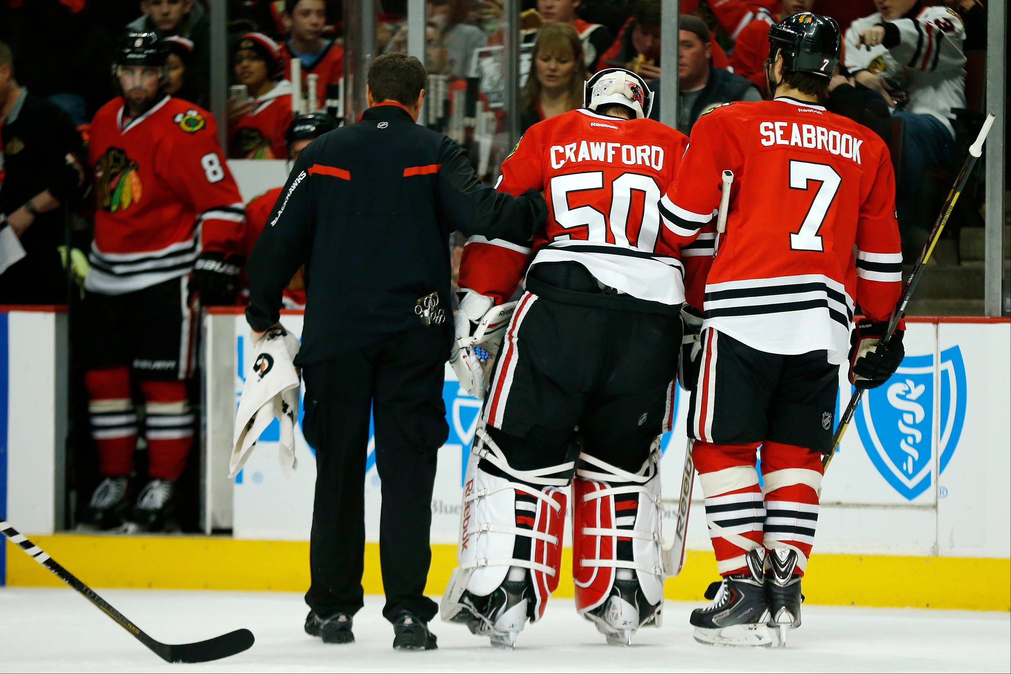 Chicago Blackhawks goalie Corey Crawford (50) is helped off the ice after suffering an injury against the Florida Panthers last Sunday. Team officials said Tuesday he will miss three weeks.