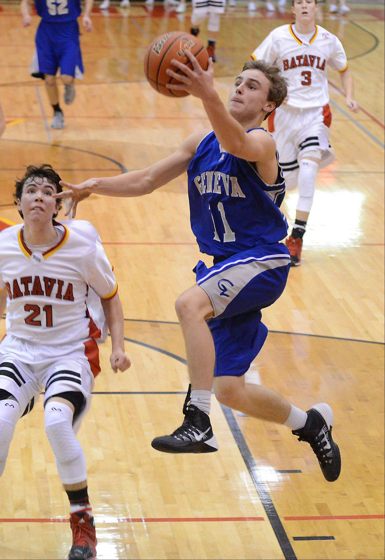 Geneva's Cam Cook (11) drives to the basket past Batavia's Jeremy Schoessling (21) during Friday's game in Batavia.