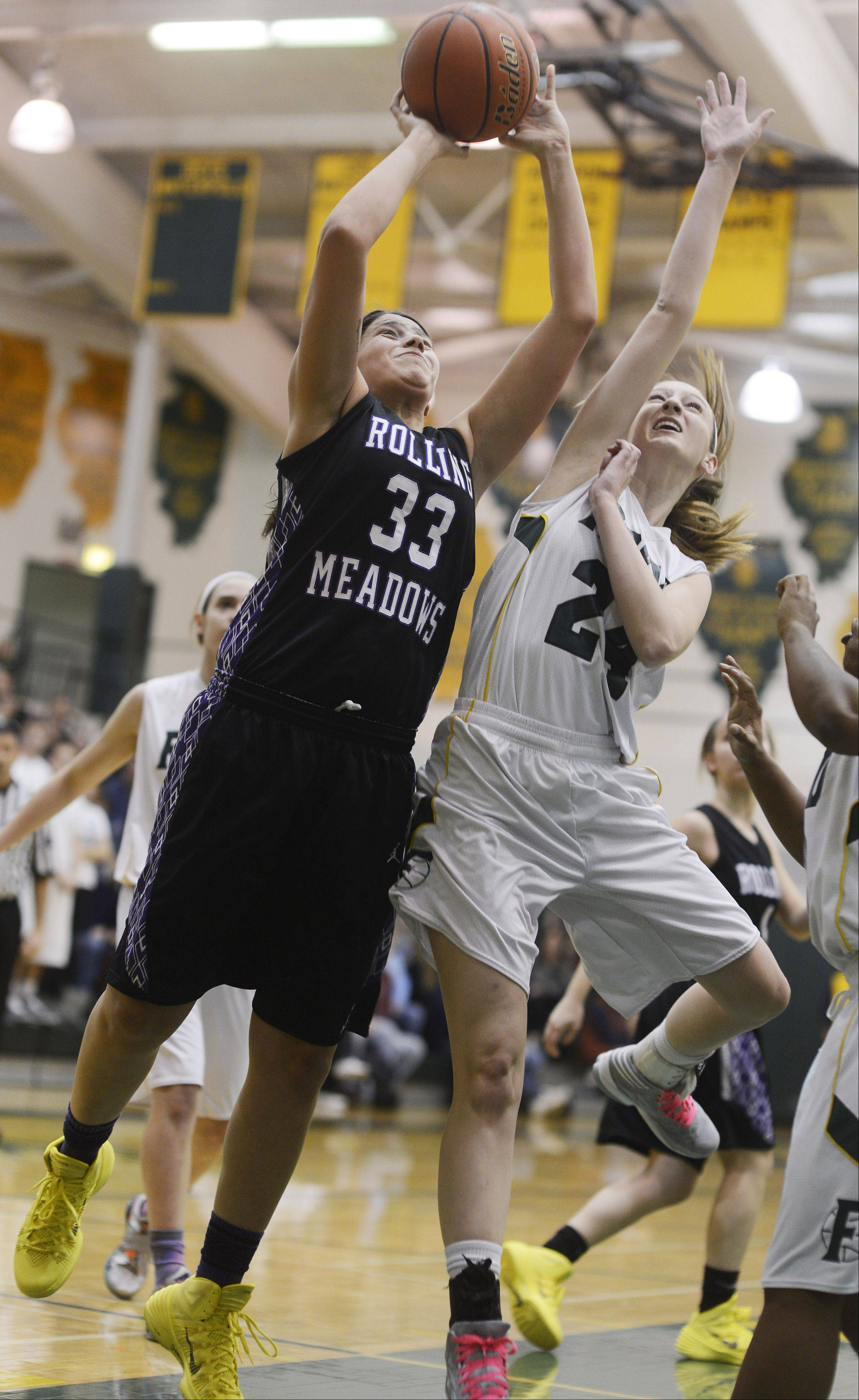 Rolling Meadows' Ashley Montanez, left, makes a strong move to the basket as Fremd's Hanna Labarge attempts the block.