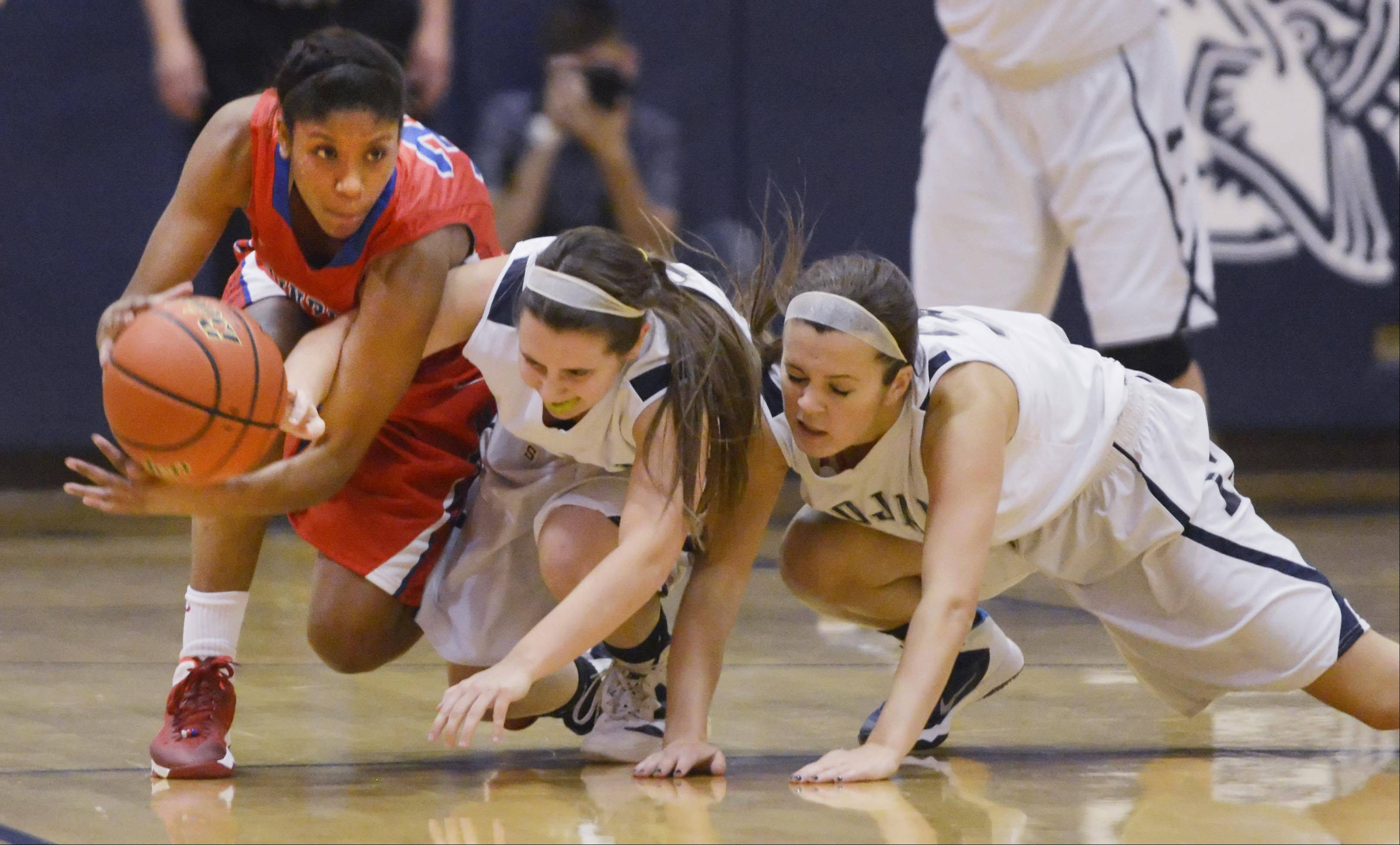 Dundee-Crown's Kayla Lawernce and Cary-Grove's Amy Clemment and Chrissy Sopchyk fight for a loose ball Tuesday in Cary.