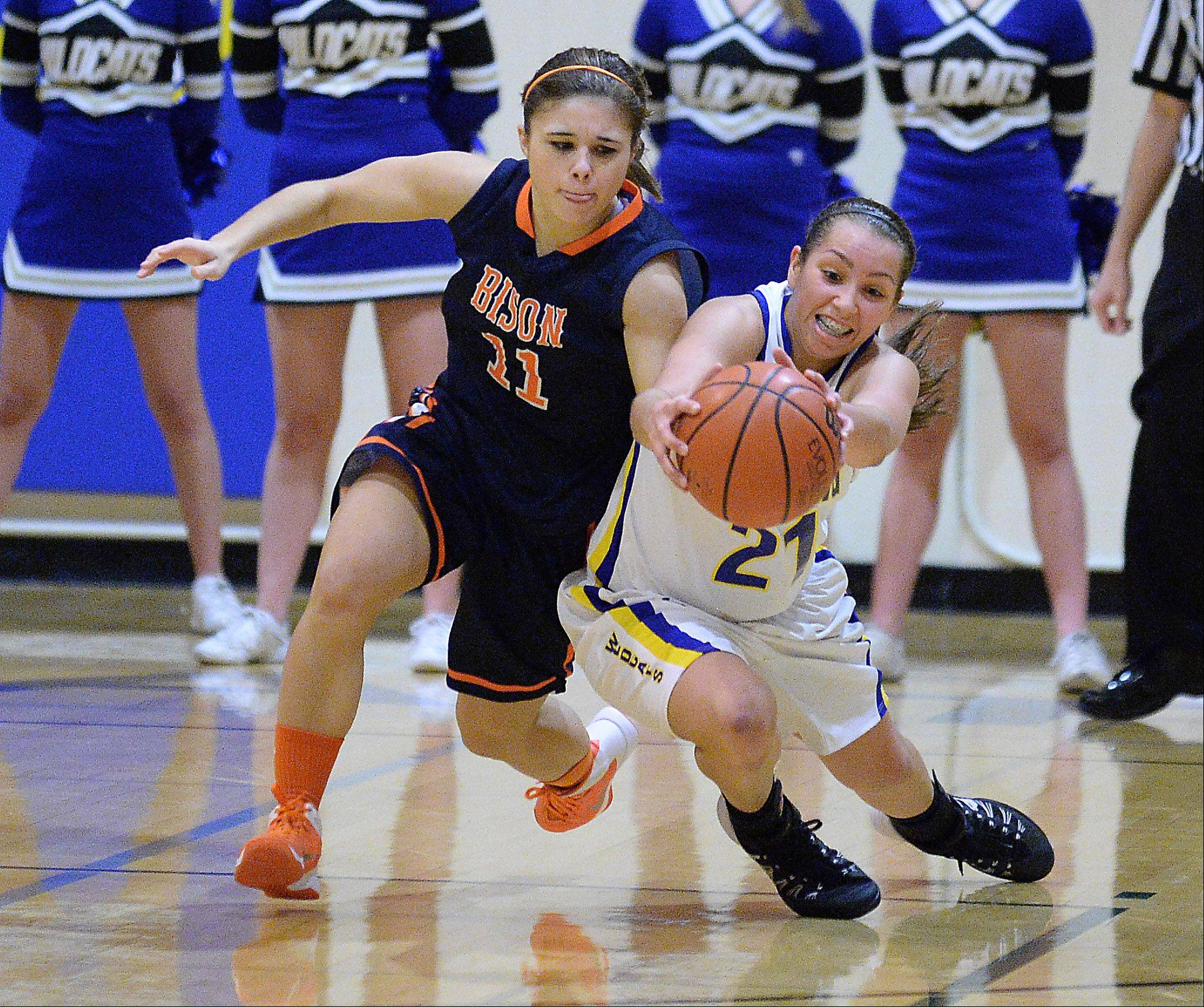 Buffalo Grove's Kim Herzog, left, and Wheeling's Deanna Kuzmanic chase a loose ball during Friday's basketball game in Wheeling.