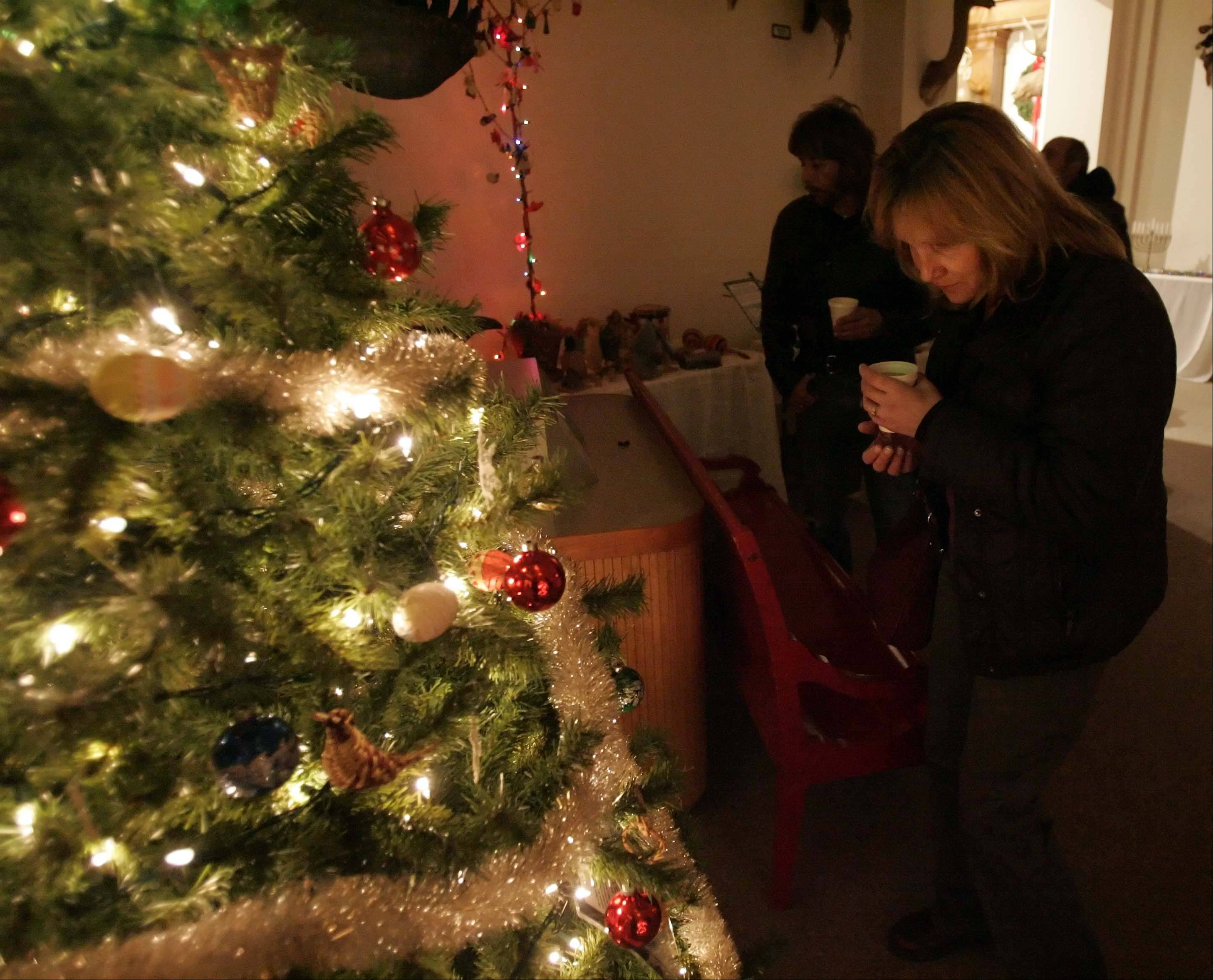 Mary Martinez of Elgin checks out holiday decorations while sipping cider at a previous Ancient Cultural Traditions and the Solstice program at the Elgin Public Museum. This year�s program will be held Saturday, Dec. 21.
