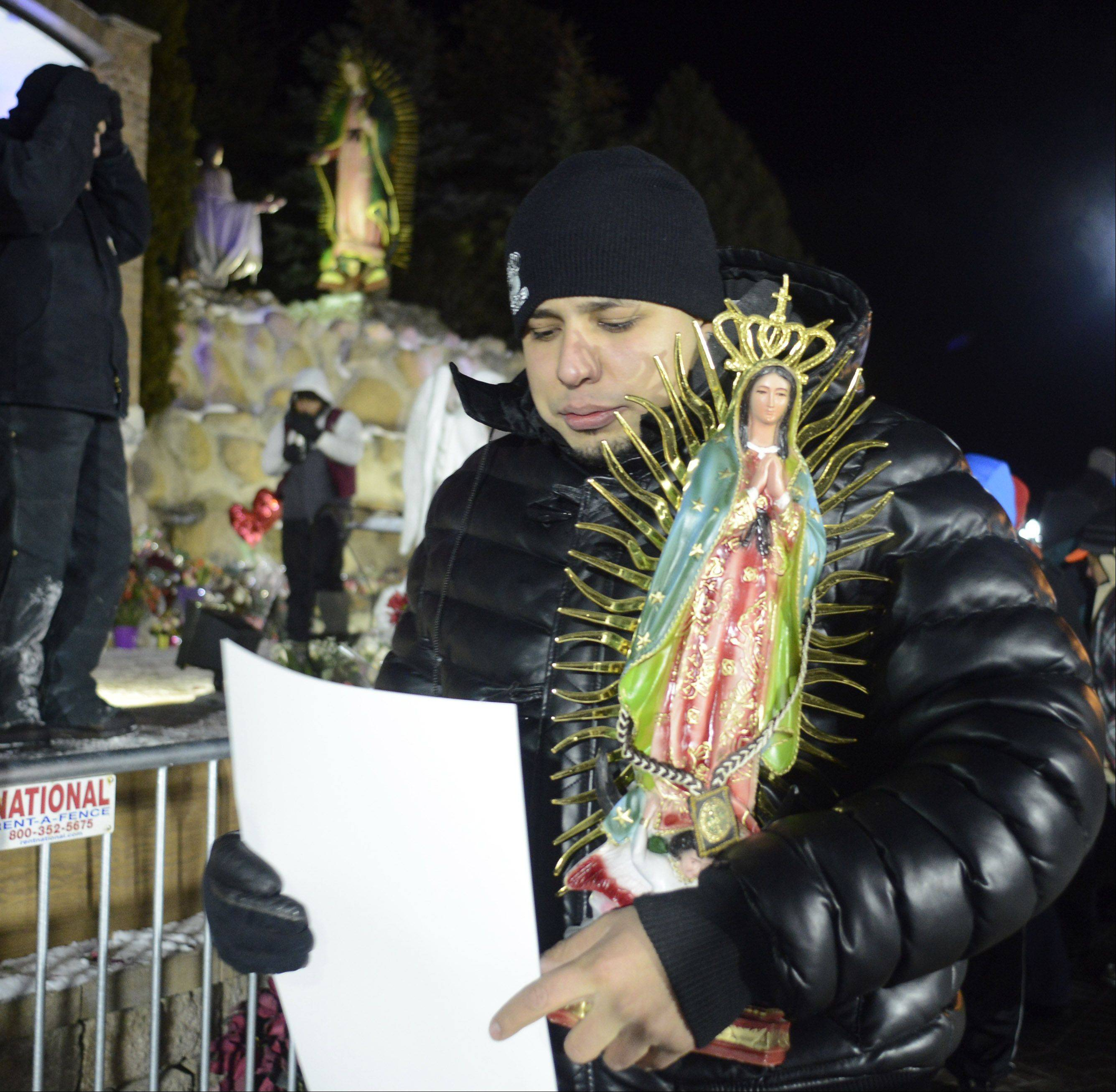 Edgar Pena of Palatine carries a statue of Our Lady of Guadalupe after visiting the at the Shrine at Maryville in Des Plaines.