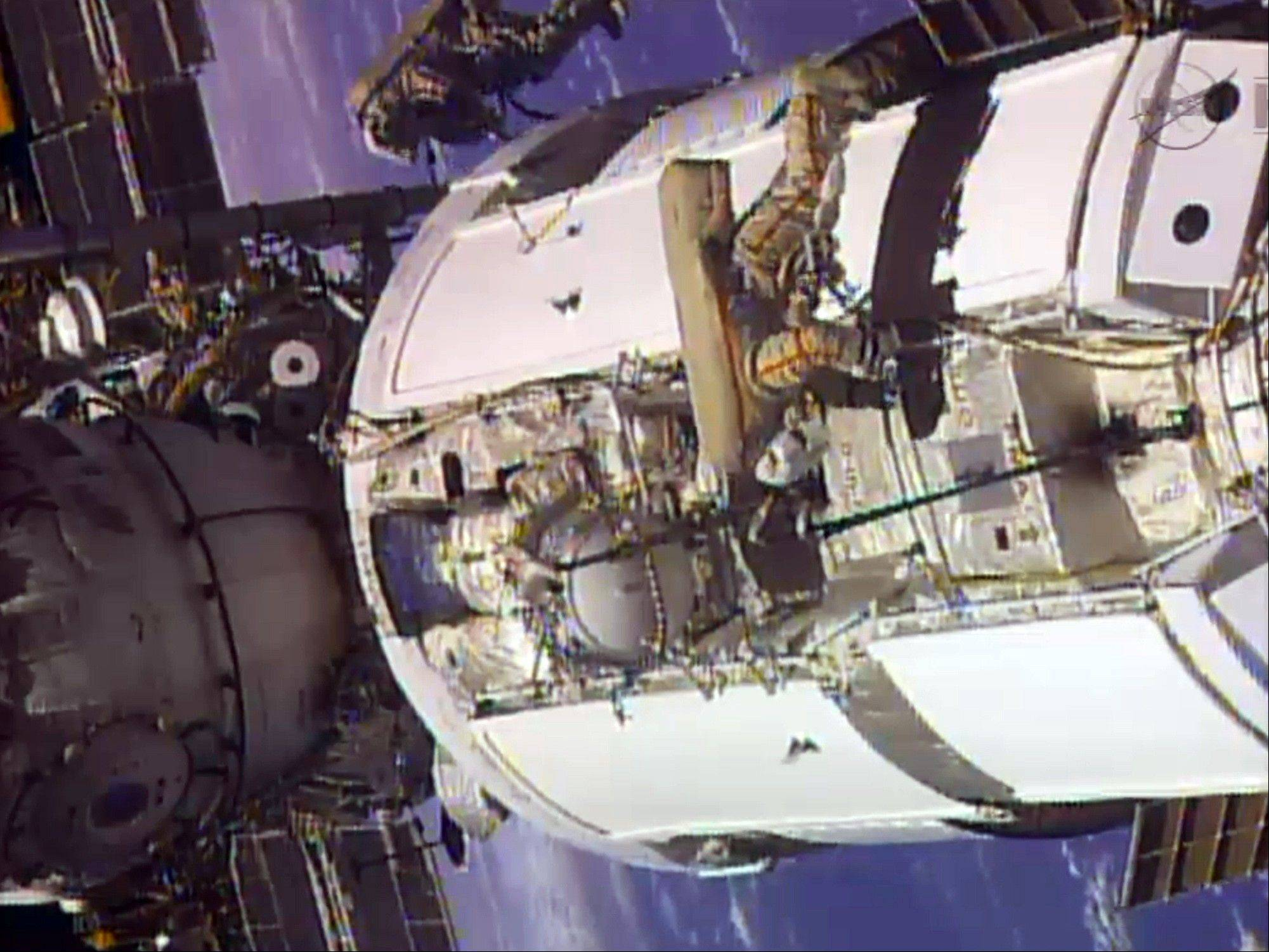 FILE - In this frame grab from video provided by NASA, two Russian flight engineers perform maintenance on the International Space Station, Monday, June 24, 2013. NASA said Wednesday it is looking into a problem with a malfunctioning cooling pump on the International Space Station, but there is no immediate danger to the six crewmen on board.