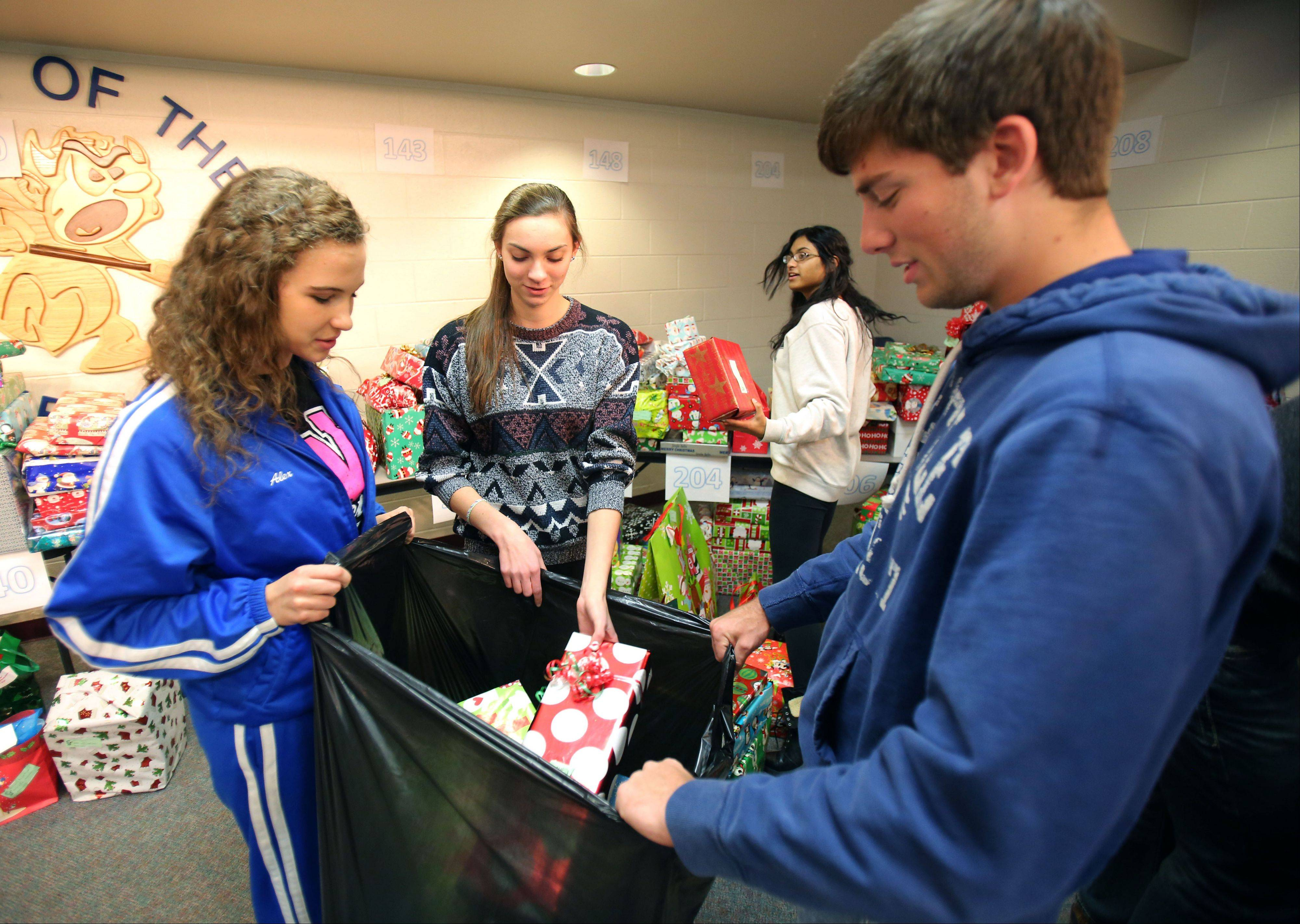 Warren Township High School seniors Alex Landry, left, Anna Baio, Connor Tangney and Christine Rajan sort wrapped Christmas presents into bags for their Letters for Santa Program. The presents will be delivered to the Reilly School in Chicago.