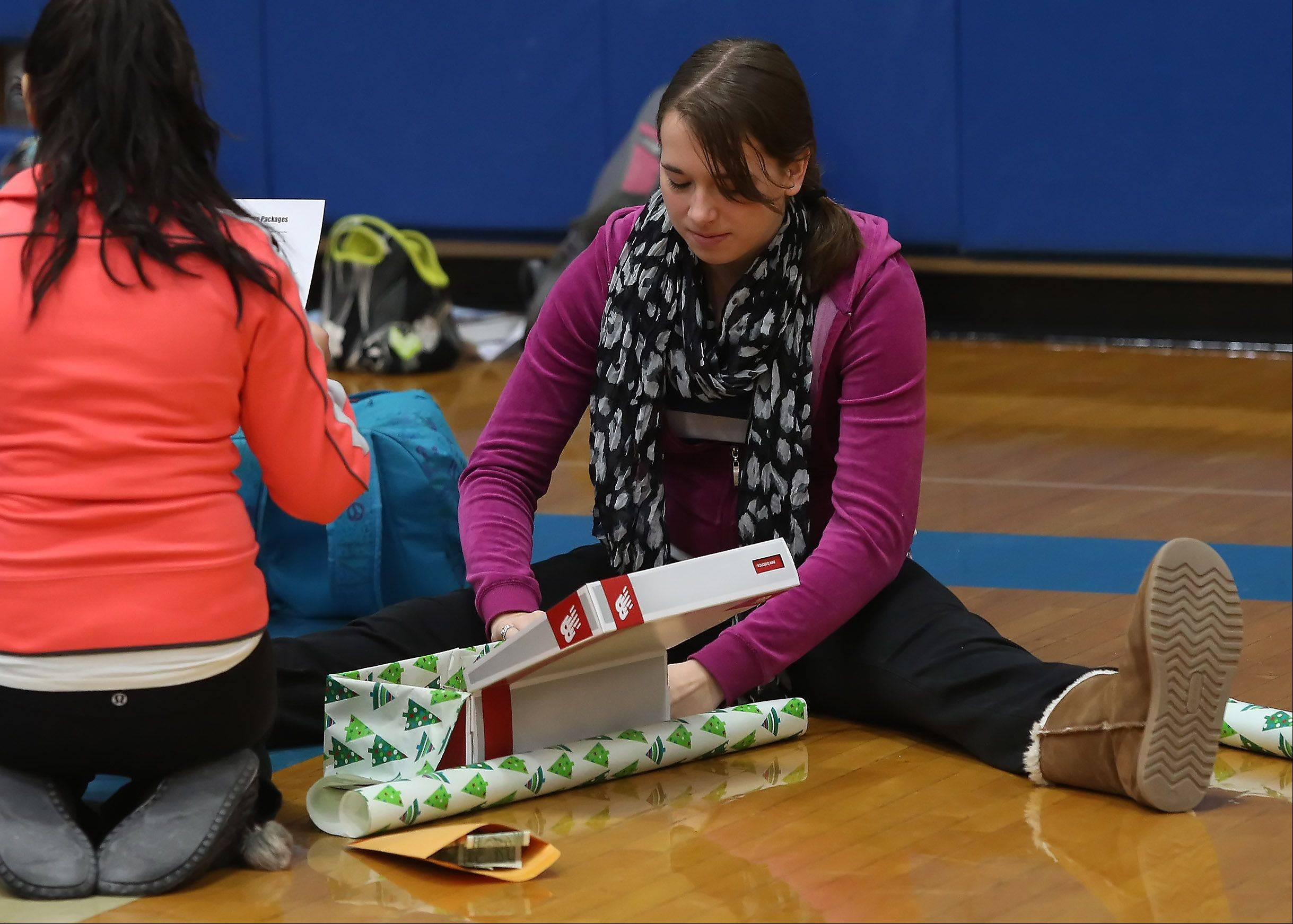 Vernon Hills High School senior Kristina Kliver wraps a shoe box filled with supplies for the COVE Care Package Program on Wednesday. Nearly 350 boxes were collected for students at the Cove Alliance school in Kapeeka, Uganda.