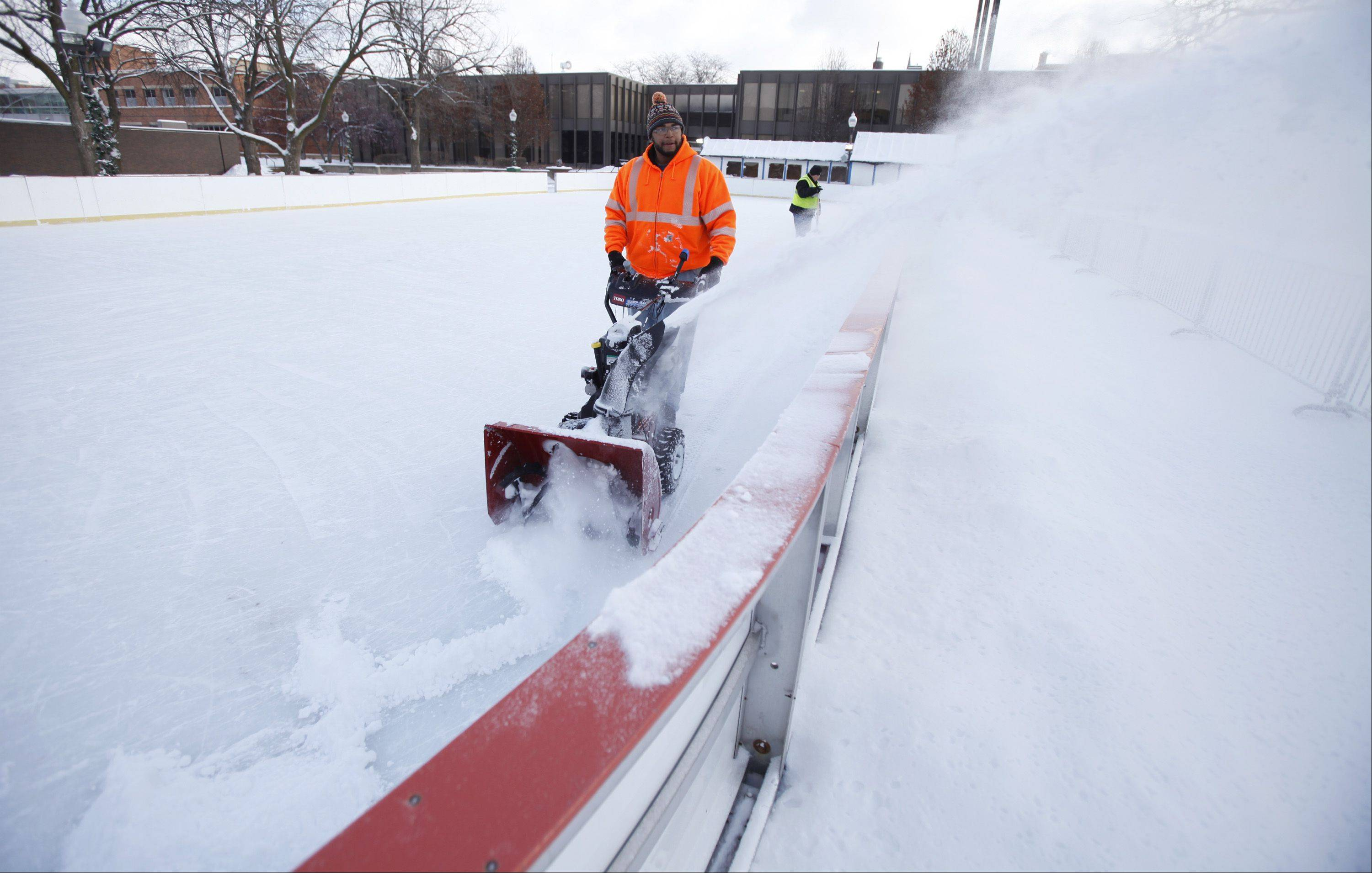 City employee Jeffrey Lewis uses a snow thrower to clear the last of the overnight snow Wednesday morning from the City Skate rink in downtown Elgin.