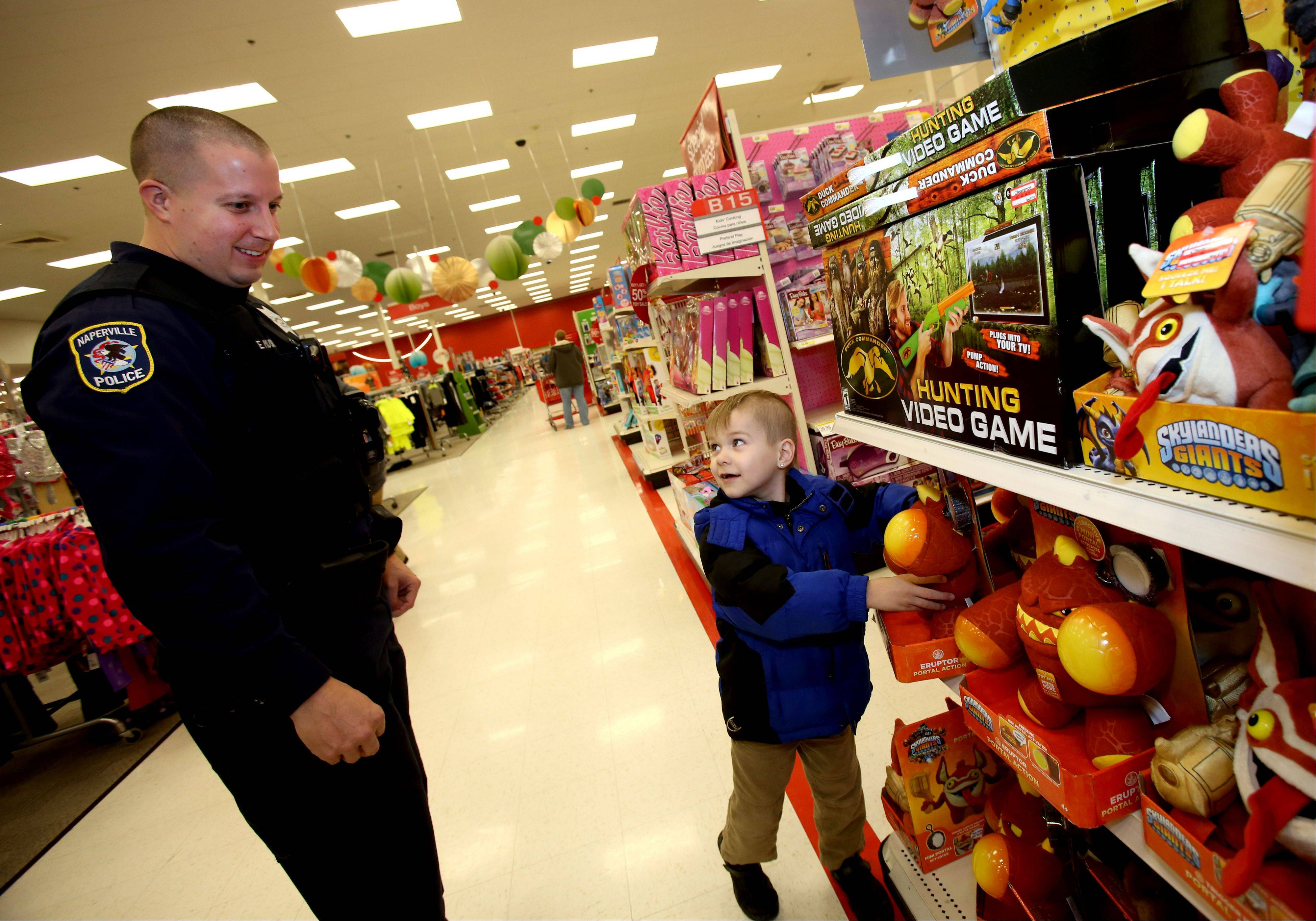 Five-year-old Xander Rambo shows Naperville police officer Eric Muska a toy as he takes part in the annual Cops With Kids event at the Super Target in Naperville.
