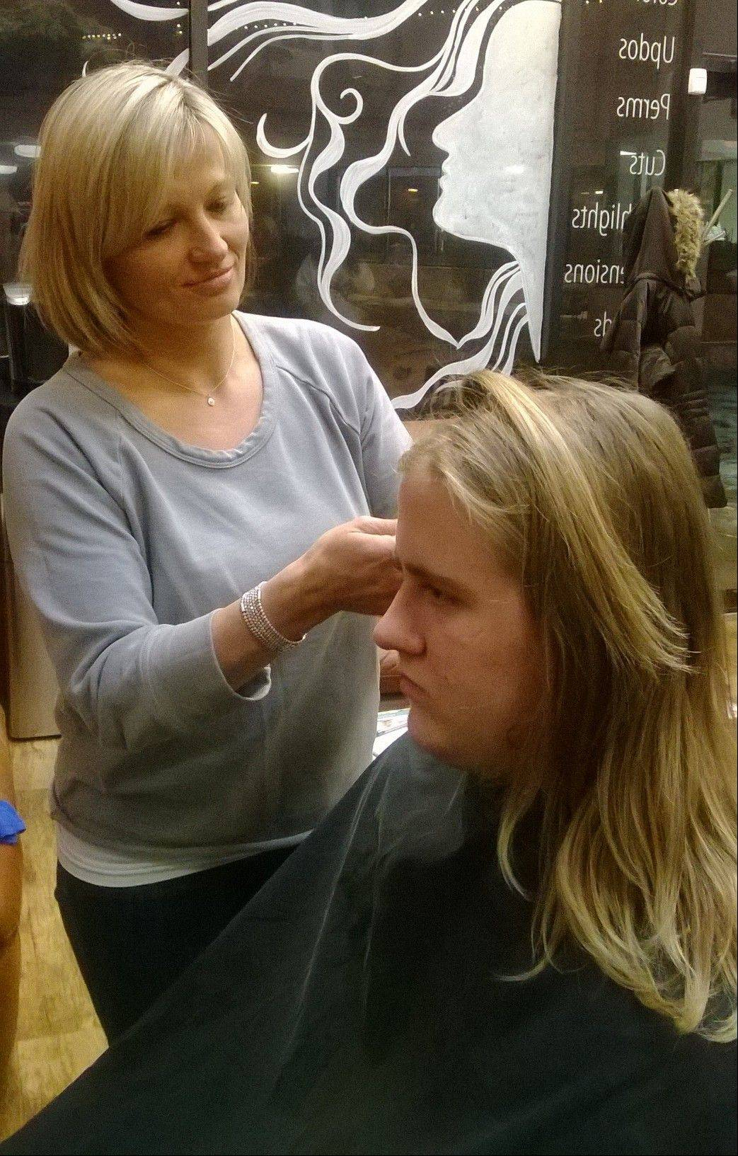 Lake Zurich senior football player Eric Gruninger gets his hair cut Tuesday by Magda Szewczyk, owner of Studio M in Lake Zurich.