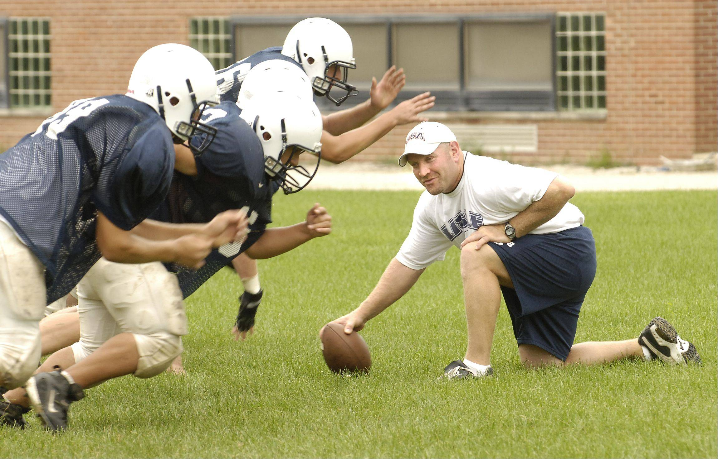 Dan Sanko, the head coach of the Lisle varsity football team, runs a drill during practice Wednesday.
