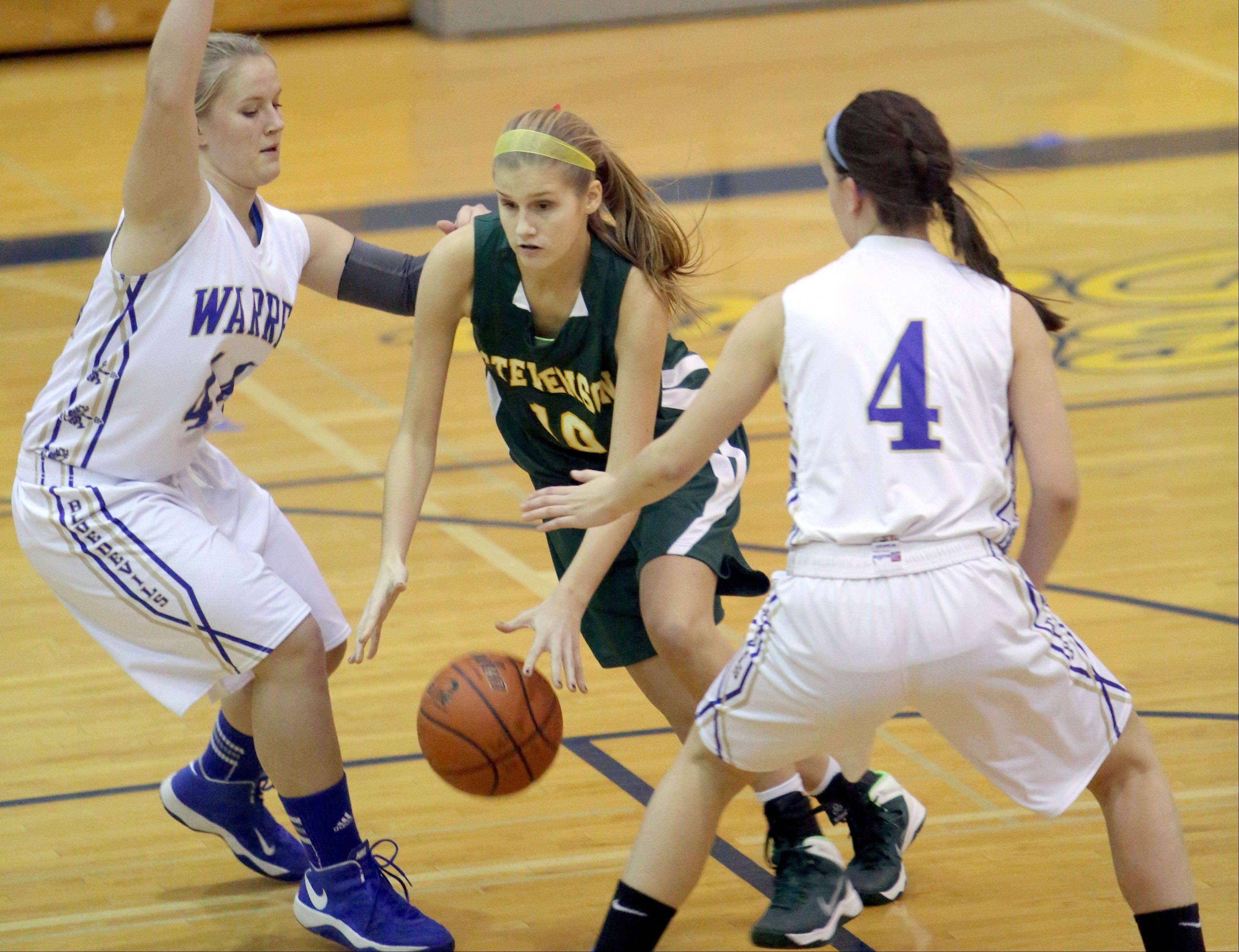 Stevenson�s Chloe Ekenberg, middle, drives through Warren�s Keely Knobbe, left, and Kylie Nedelka during their game Tuesday night in Gurnee.