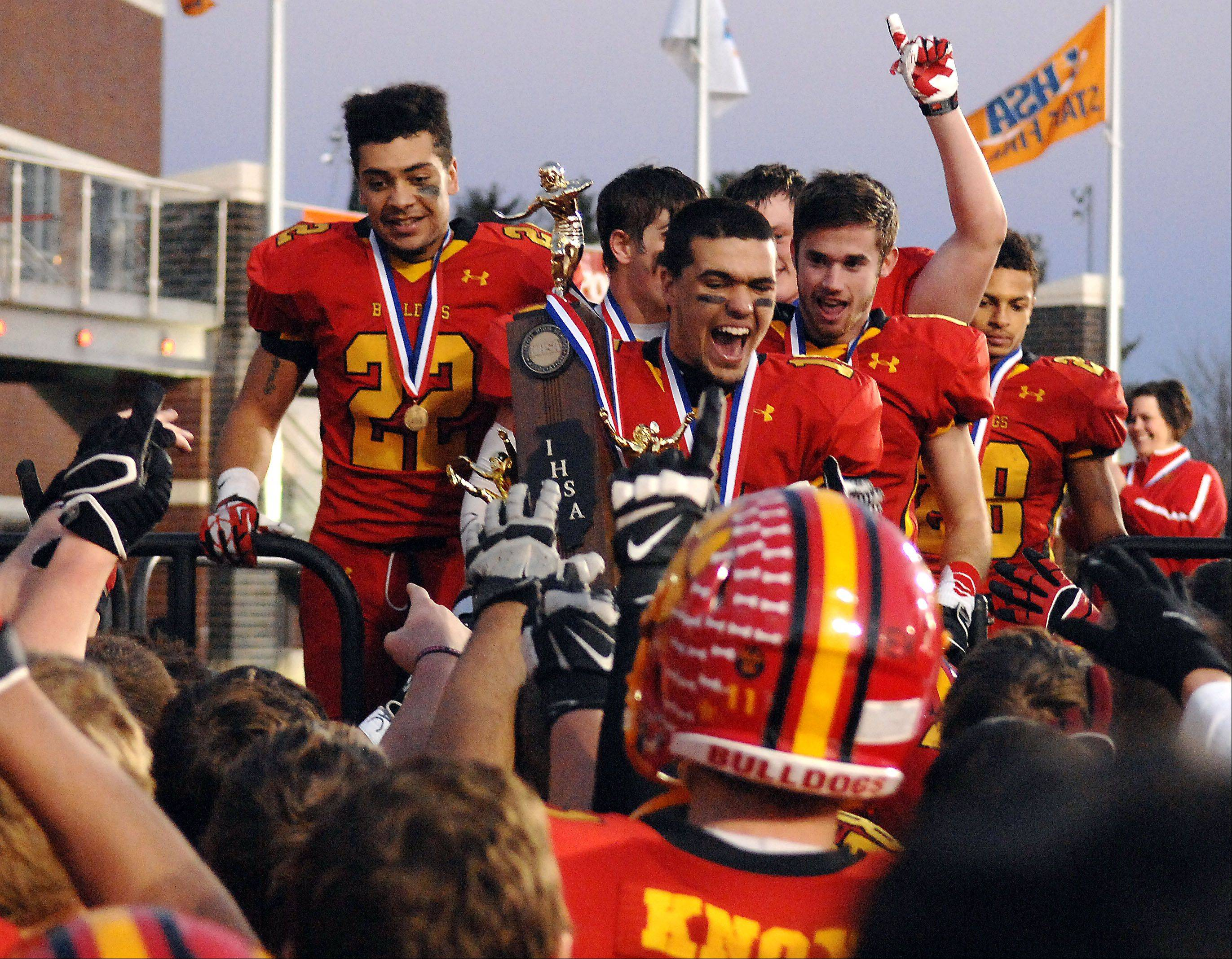 Batavia's Micah Coffey (15) brings the 6A championship trophy to his teammates after beating Richards in DeKalb.