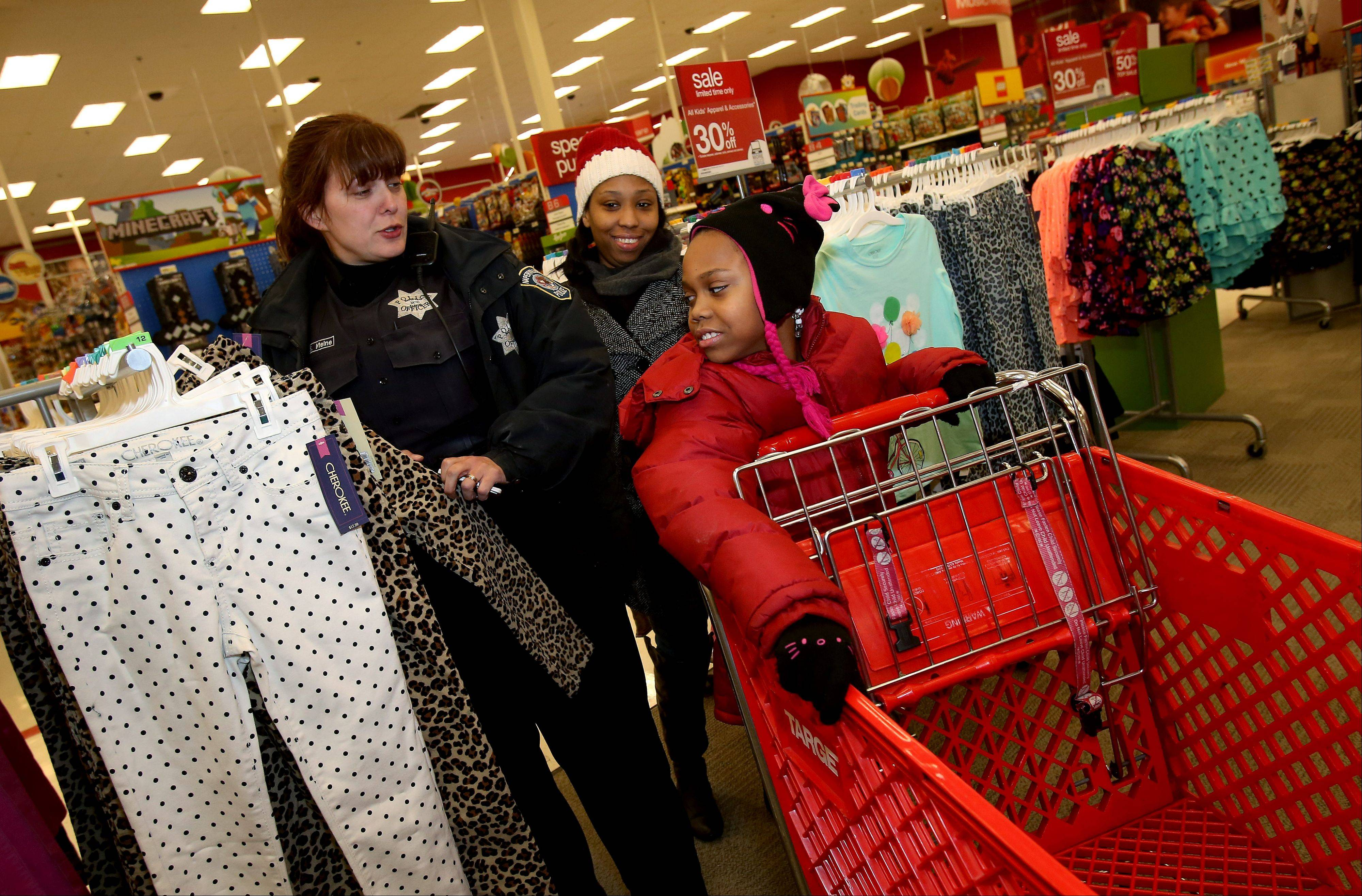 Naperville police officer Sherry Meine takes Carissa Blackwell and her 9-year-old daughter, Christiona, to look at clothes during the Cops with Kids event Tuesday at the Super Target in Naperville.