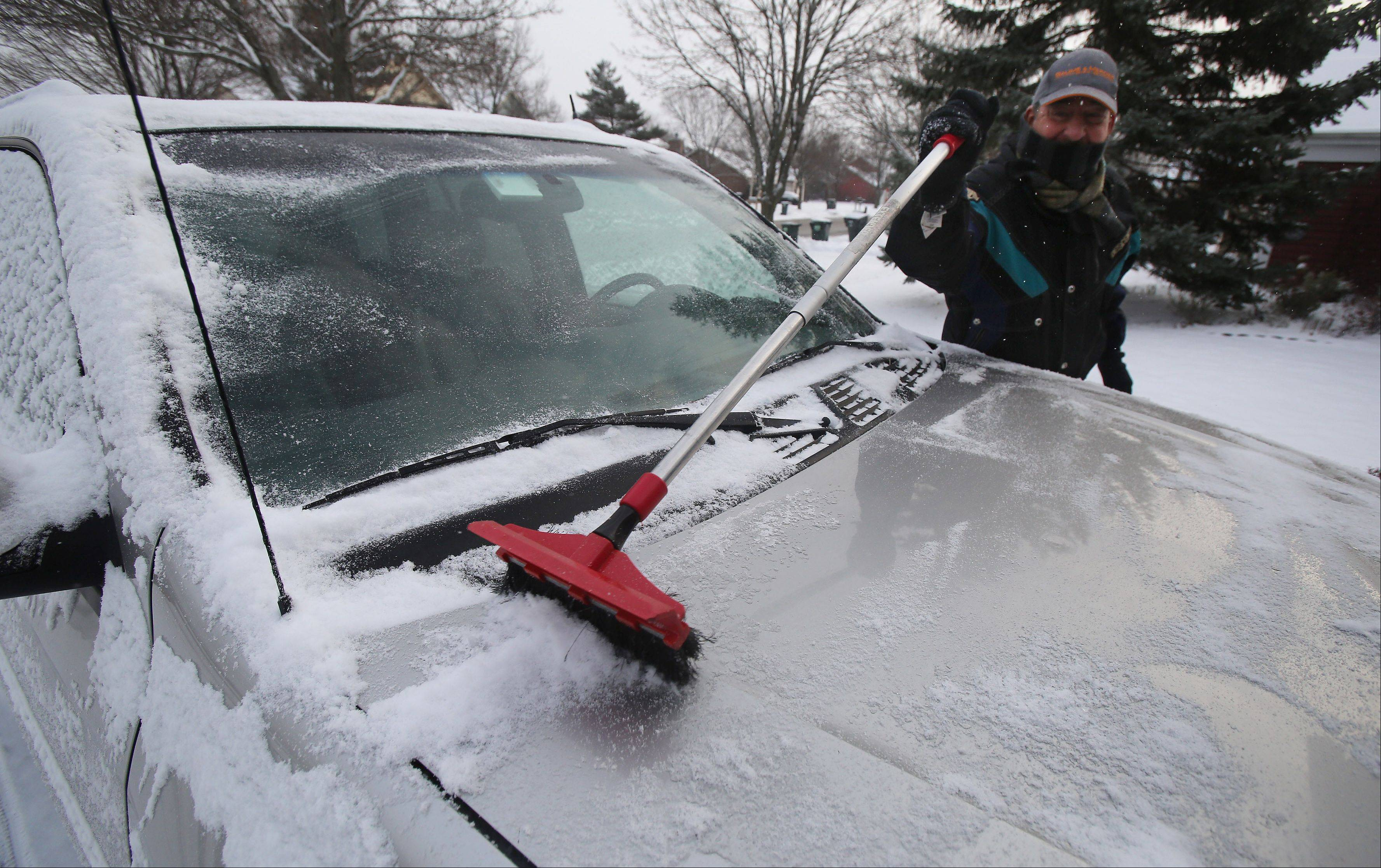 Mundelein resident Steve Kern clears the snow off his SUV after snow fell in Lake County Wednesday. Snow plows were out in force clearing streets during the early morning hours to help with commuter traffic.