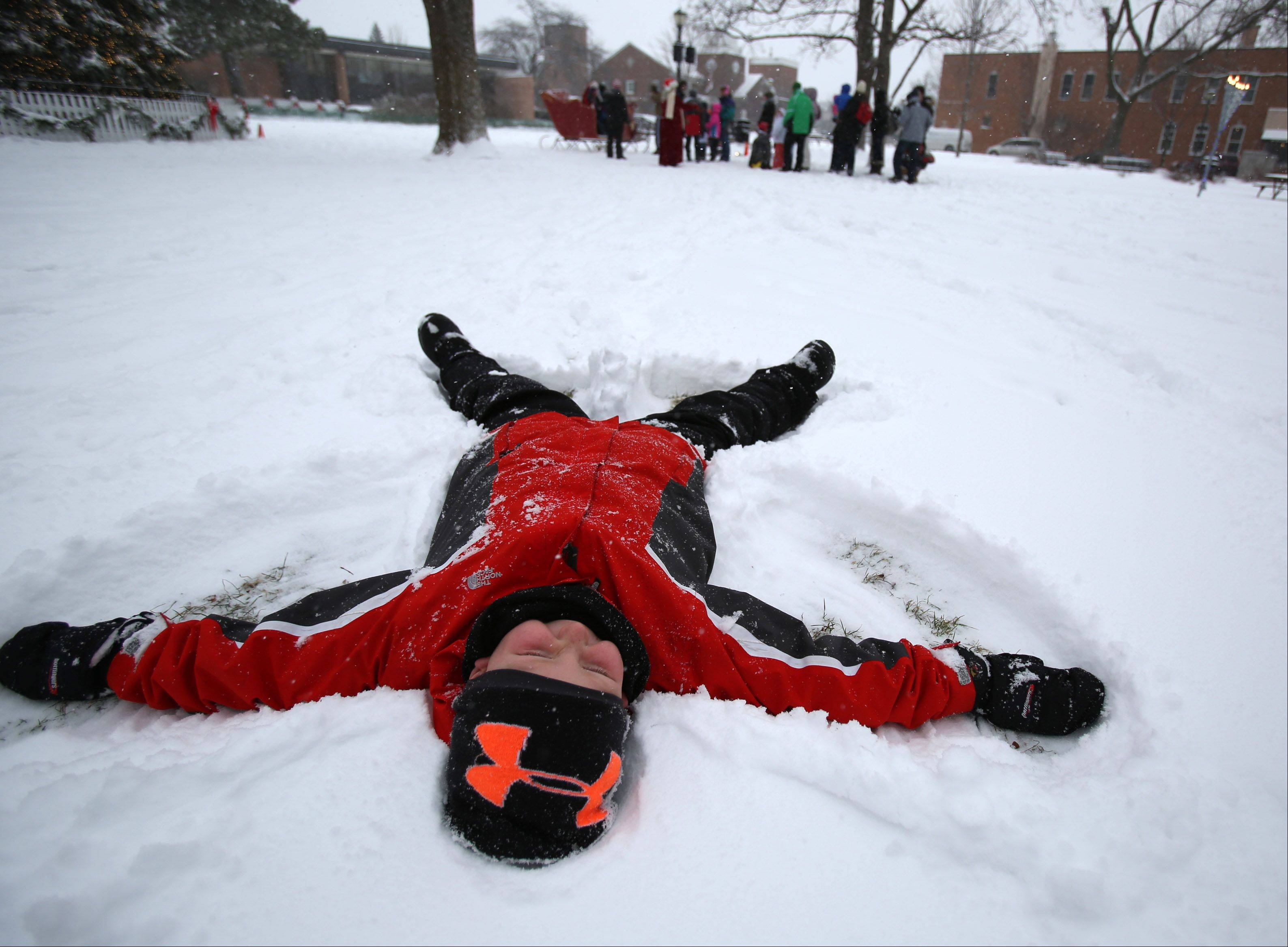 Ethan Schoenfeld, 9, of Libertyville makes a snow angel after visiting with Santa Claus in Cook Park during Dickens of a Holiday Festival on Saturday in Libertyville.