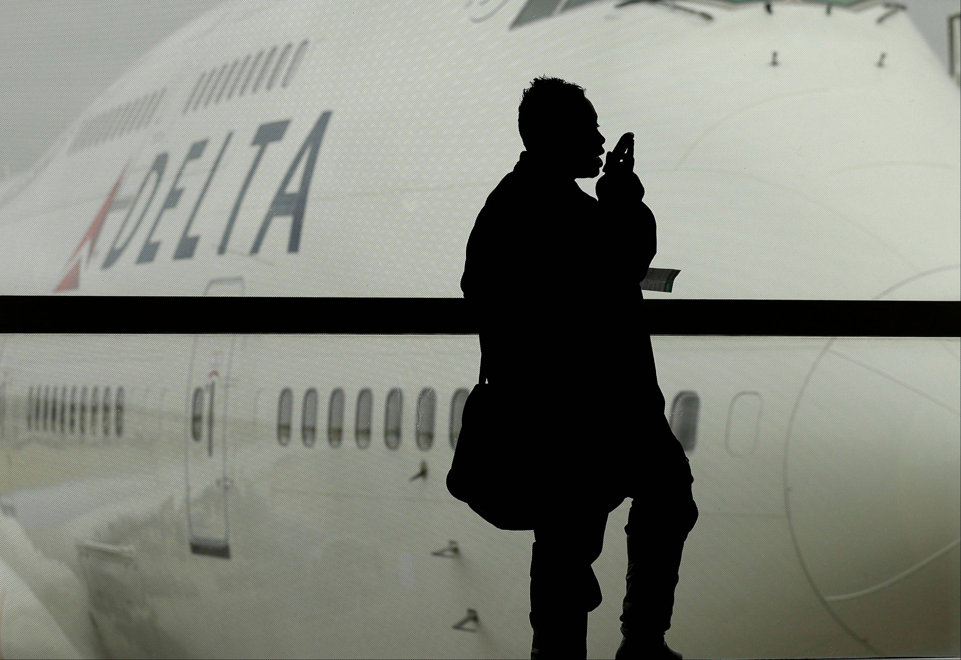 A traveler on Delta Airlines waits for her flight in Detroit. As federal regulators consider removing a decades-old prohibition on making phone calls on planes, a majority of frequent air travelers oppose such a change, a new Associated Press poll found Wednesday.