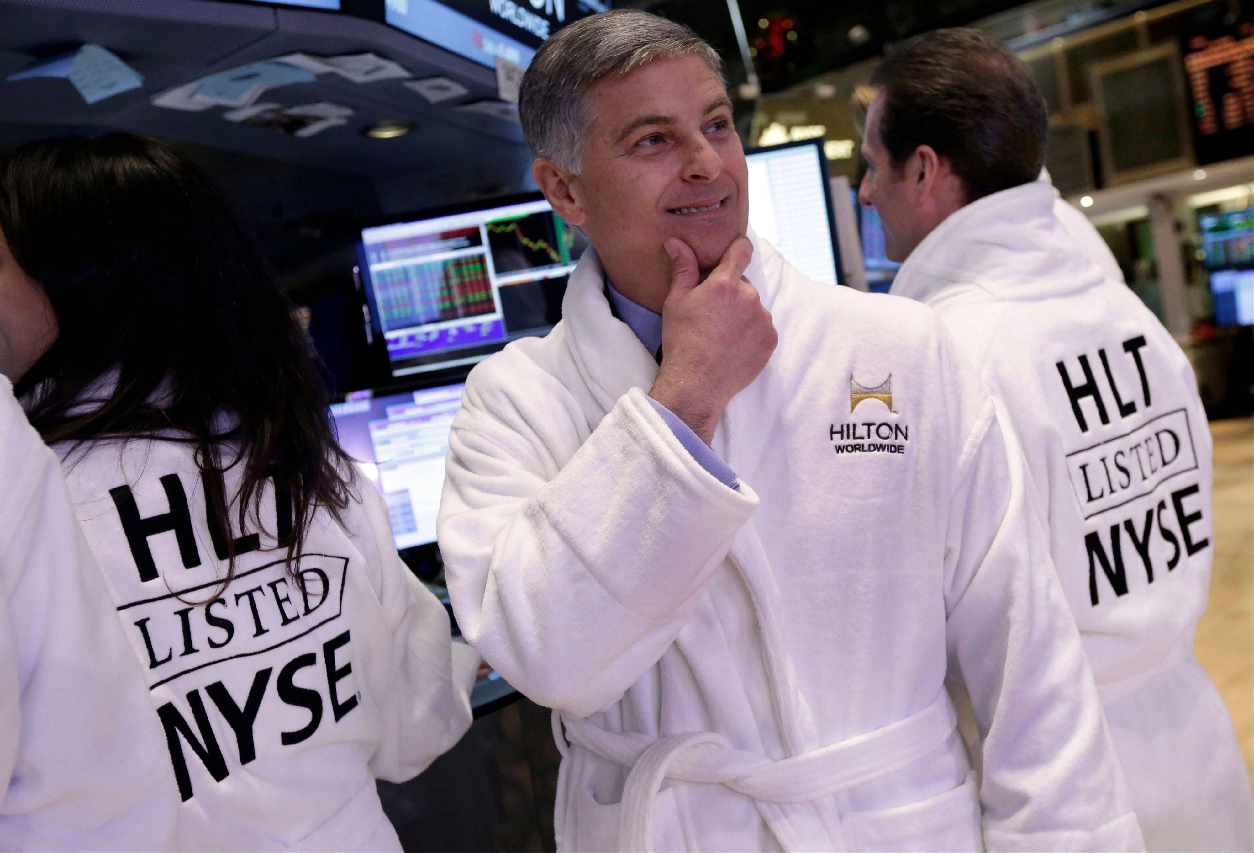 CEO of Hilton Worldwide Christopher Nassetta, center, poses in a Hilton robe after his company's IPO began trading on the floor of the New York Stock Exchange Thursday. Hilton Worldwide Holdings Inc. is the world's largest hotel group, with 665,667 rooms across 90 countries and territories.