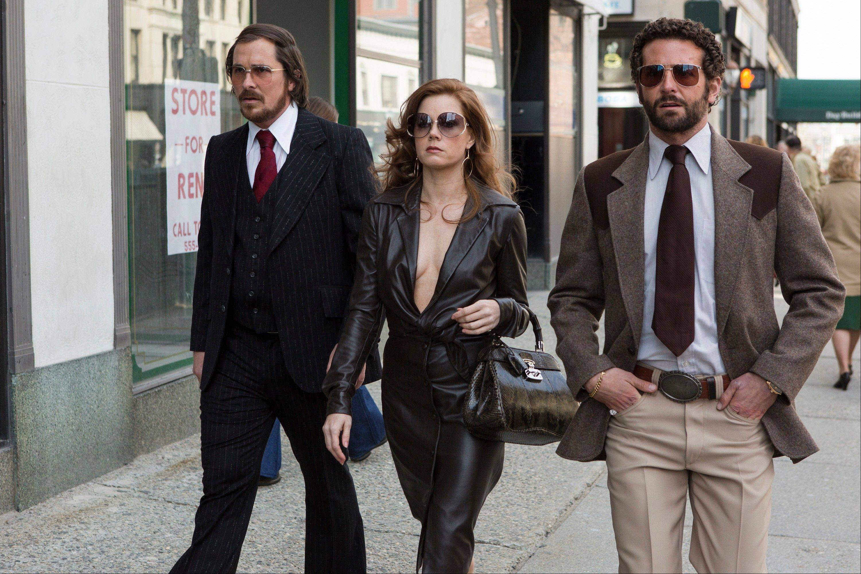 "Christian Bale, left, Amy Adams and Bradley Cooper star in ""American Hustle,"" received seven Golden Globe nominations Thursday."