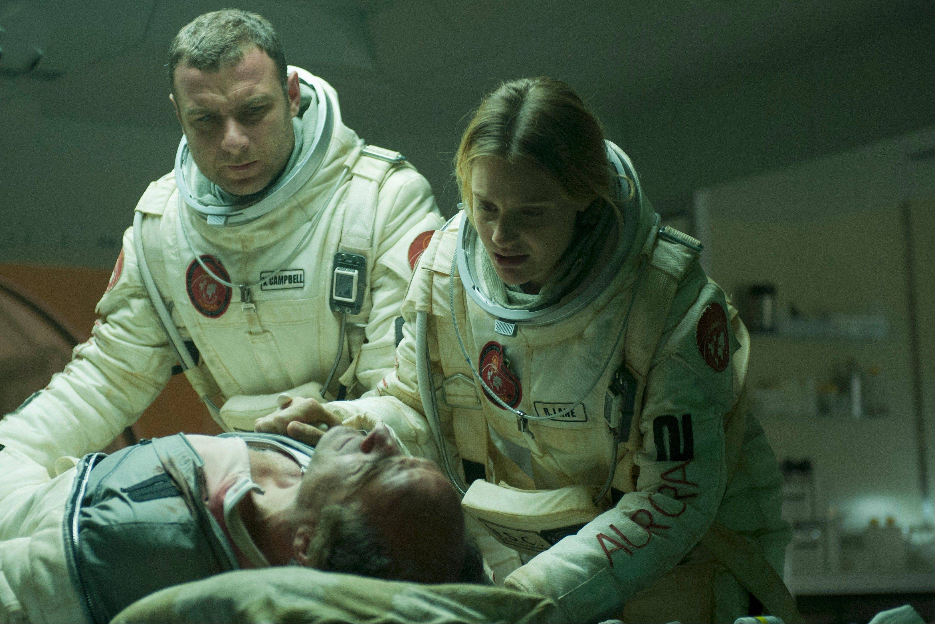 "Commander Robinson (Liev Schreiber) and a medic (Romola Garai) help an infected astronaut (Elias Koteas) in the sci-fi horror film ""The Last Days on Mars."""