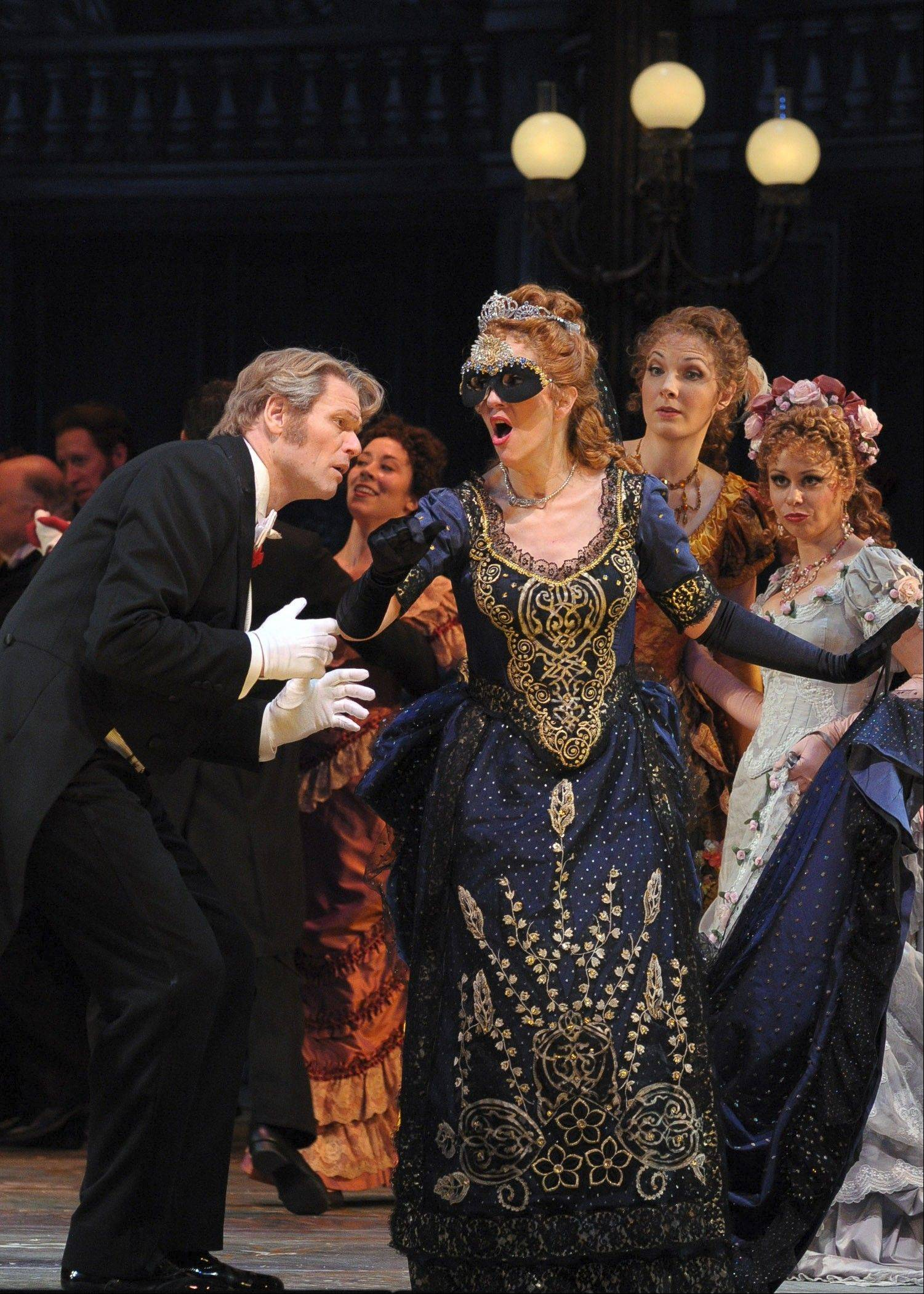"Gabriel von Eisenstein (Bo Skovhus) is befuddled by a masked Hungarian countess (actually Juliane Banse as his wife, Rosalinde) as sisters Ida (Julie Anne Miller) and Adele (Daniela Fally) look on at Prince Orlofsky's party in the Lyric Opera of Chicago's ""Die Fledermaus."""