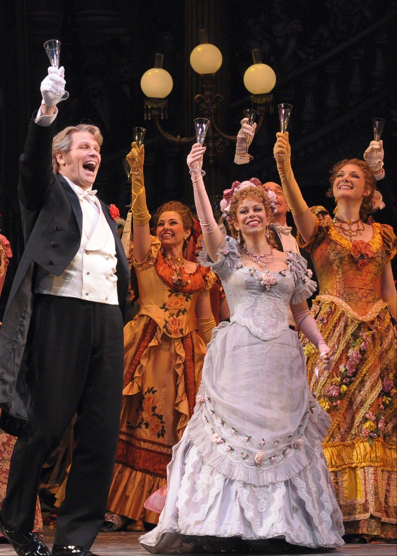 "Gabriel von Eisenstein (Bo Skovhus), left, toasts to champagne with sisters Adele (Daniela Fally in blue) and Ida (Julie Anne Miller), right, at Prince Orlofsky's party in the Lyric Opera of Chicago's comic operetta ""Die Fledermaus."""