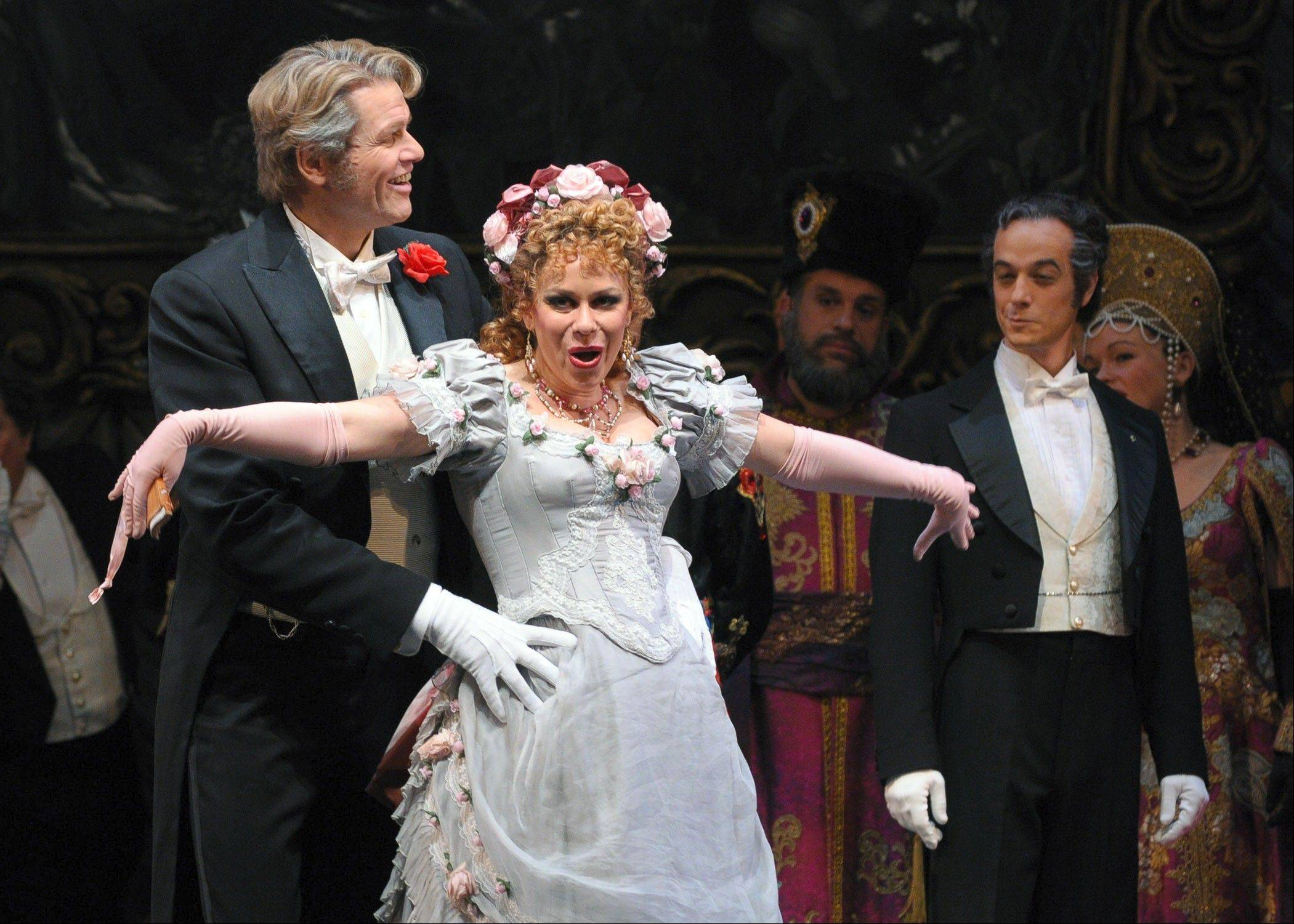 "Gabriel von Eisenstein (Bo Skovhus), left, encounters his parlormaid, Adele (Daniela Fally), as both fall into a comic trap set by Dr. False (Adrian Eröd), right, at Prince Orlofsky's party in the Lyric Opera of Chicago's production of ""Die Fledermaus."""