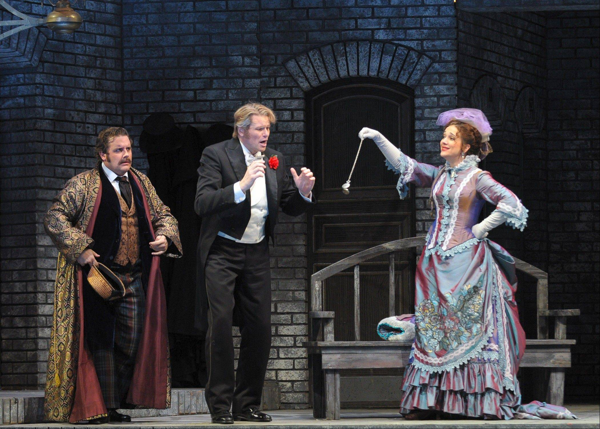 "Gabriel von Eisenstein (center) finds himself in a muddle with his wife, Rosalinde (Juliane Banse), and her former lover, Alfred (Michael Spyres), in the middle of a prison in the Lyric Opera of Chicago's ""Die Fledermaus."""
