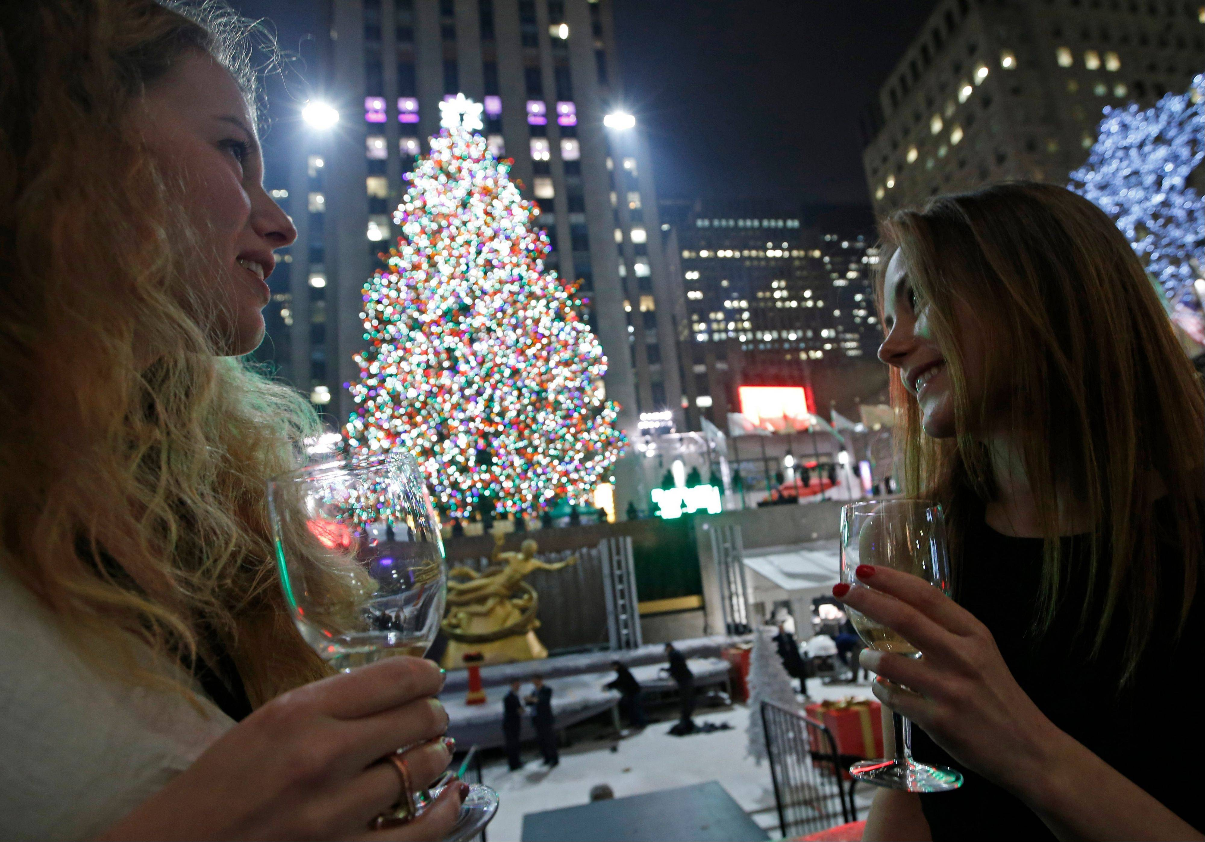 Anna Ladner, left, and Vanja Ojes Dahlberg sip Champagne in front of the Rockefeller Center Christmas tree in New York. Some 45,000 energy-efficient LED lights adorn the 76-foot tree.