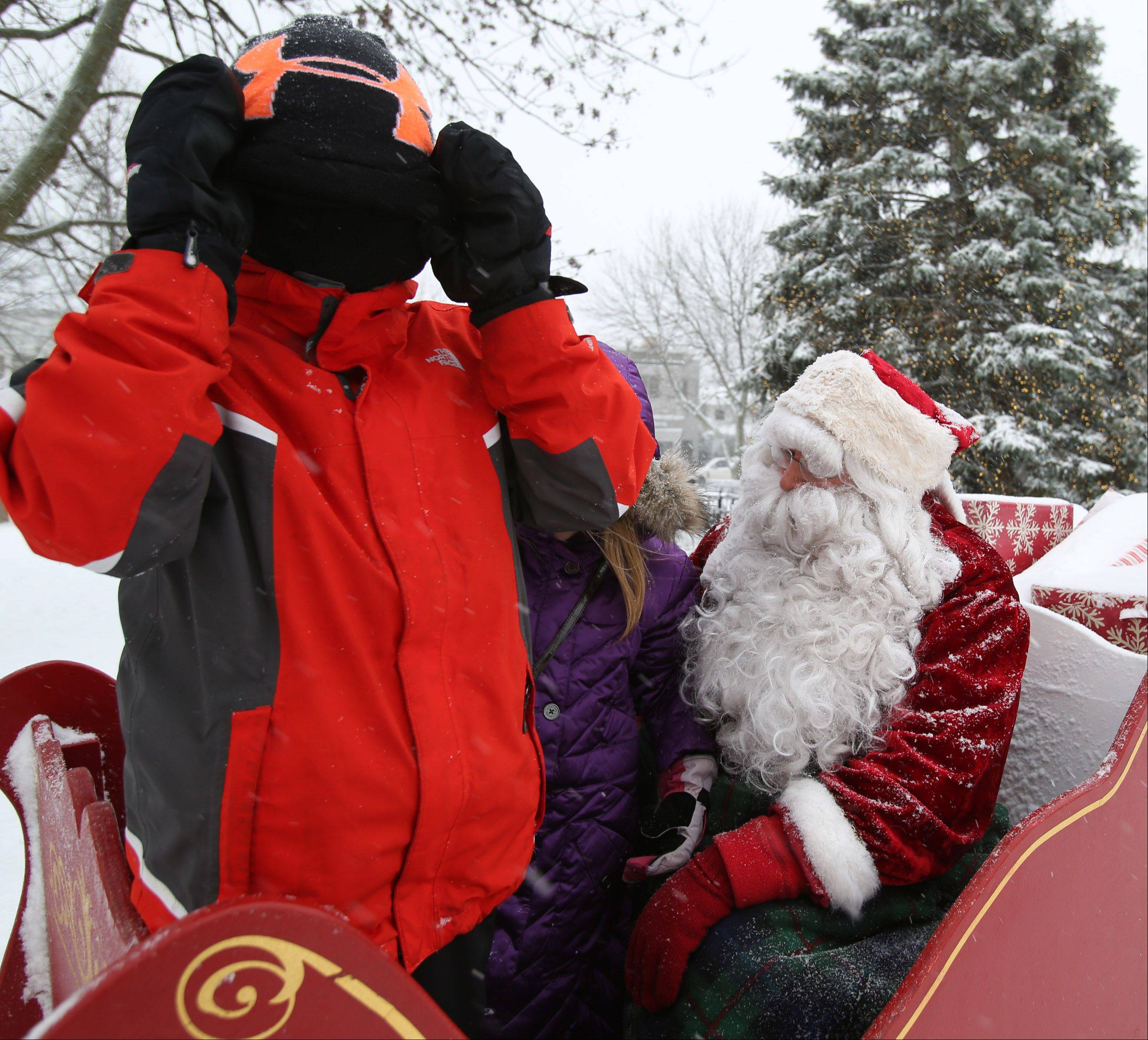 Ethan Schoenfeld, 9, covers his face, due to blowing snow, as his sister Teagan Schoenfeld, 7, both of Libertyville goes through her wish list as she visits with Santa Claus in Cook Park during Dickens of a Holiday Festival on Saturday in Libertyville.
