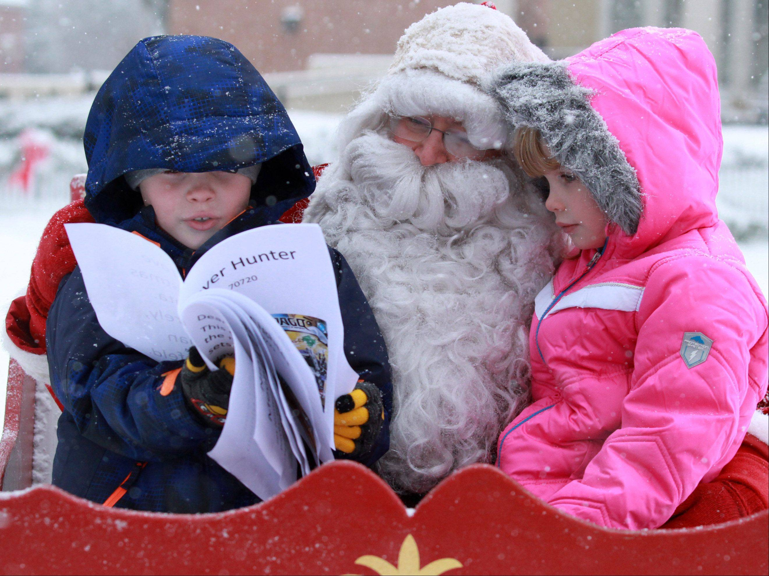 Eight-year-old Carson Nemuras made a Christmas wish list with graphics to show as he and his sister, Abbie Nemuras, 7, both of Libertyville, visit with Santa Claus in Cook Park during Dickens of a Holiday Festival on Saturday in Libertyville.