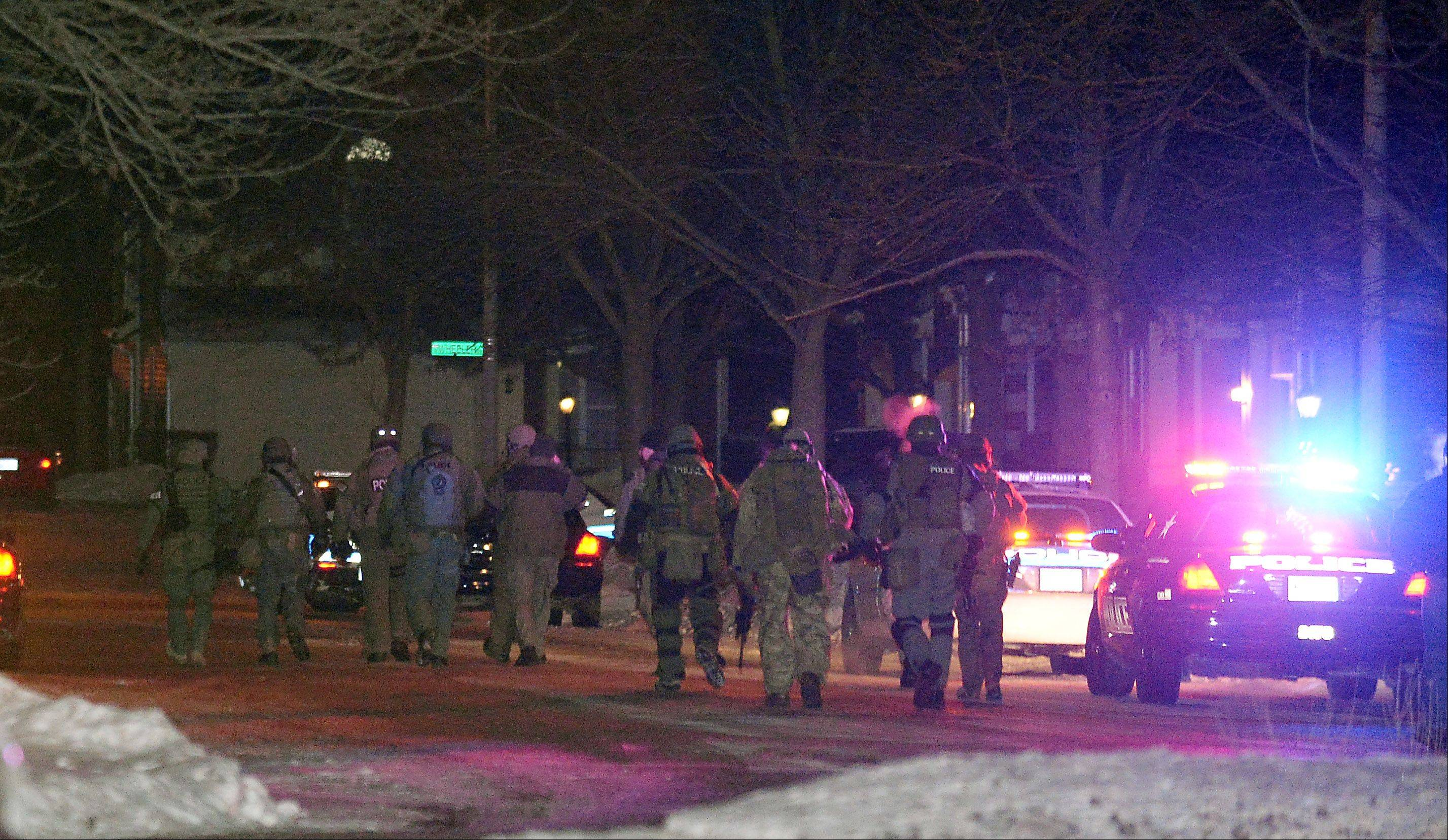 Police and tactical officers respond to a hostage situation near Arlington Heights Road and Palatine Road Thursday night. Here officers walk toward Wheeler Street.