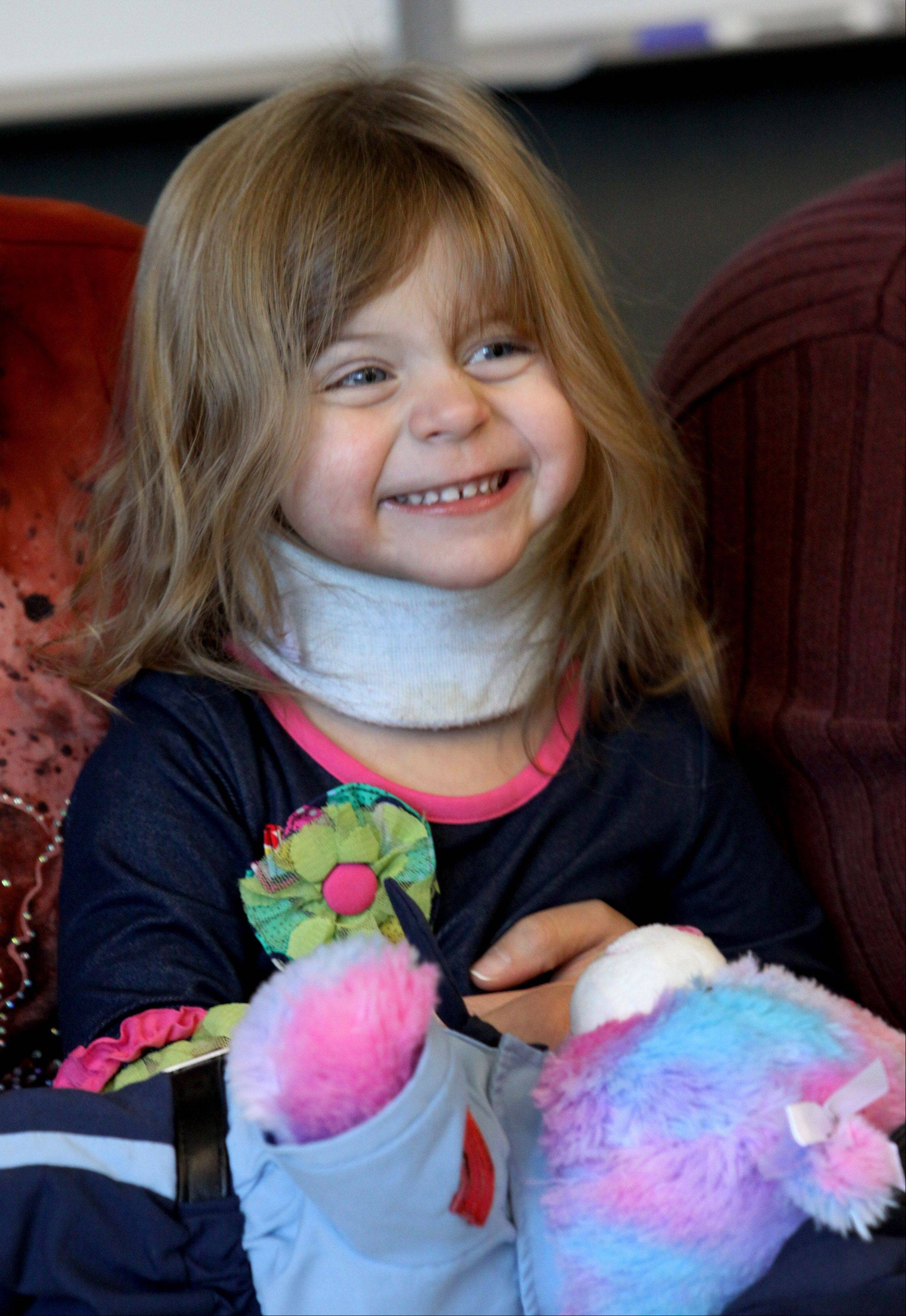 Abby Schmidt, 2, still on the mend, is all smiles Thursday at the Aurora Police Station.